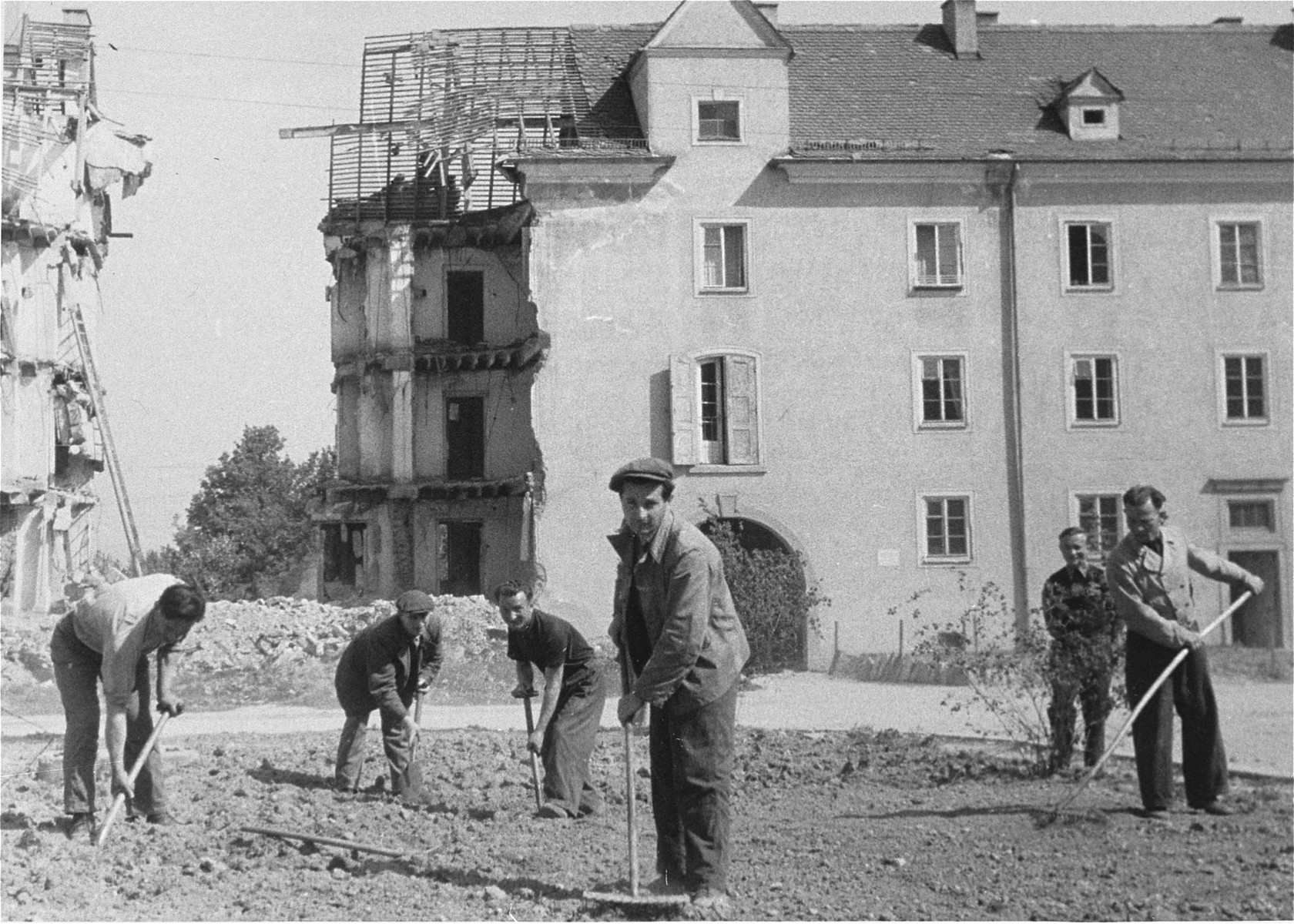 DPs dig in a field in front of a bombed out building.