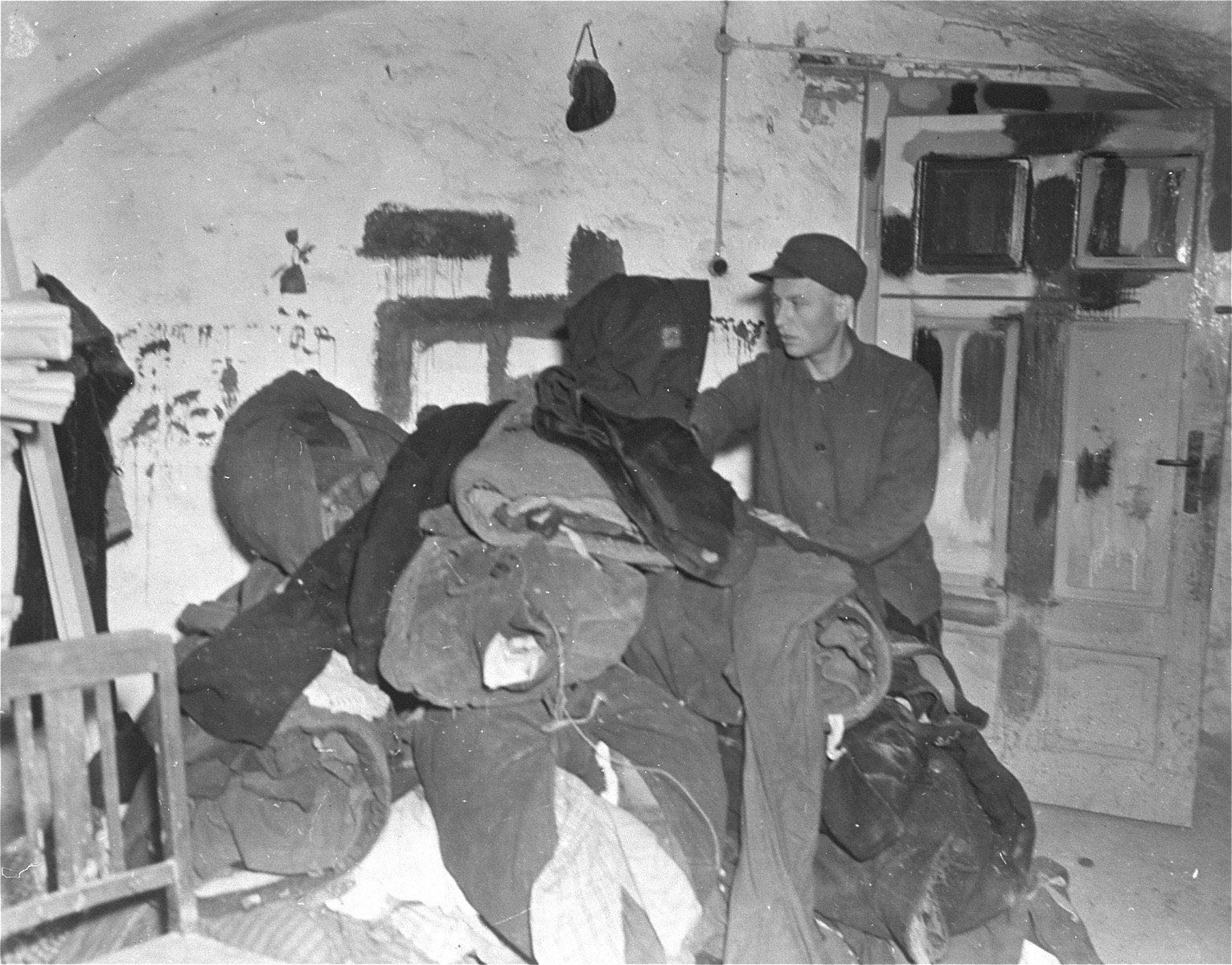 A survivor of the Hadamar Institute shows war crimes investigators a uniform belonging to a Polish prisoner that he has plucked from a pile of clothing removed from victims of the euthanasia killings.  Pictured is 30-year-old Frita Dickmann. The photograph was taken by an American military photographer soon after the liberation.
