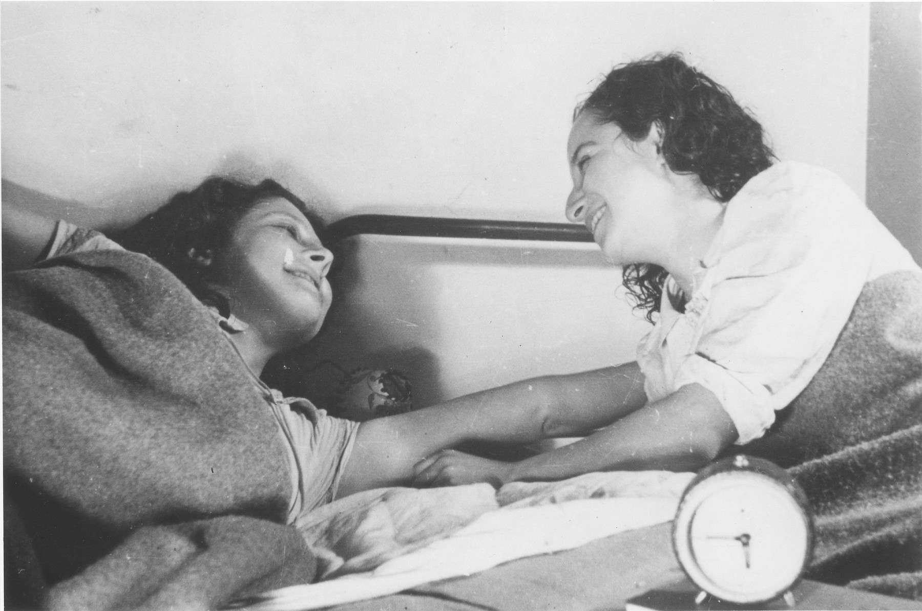 Two teenage girls converse in bed at the Le Tremplin children's home.