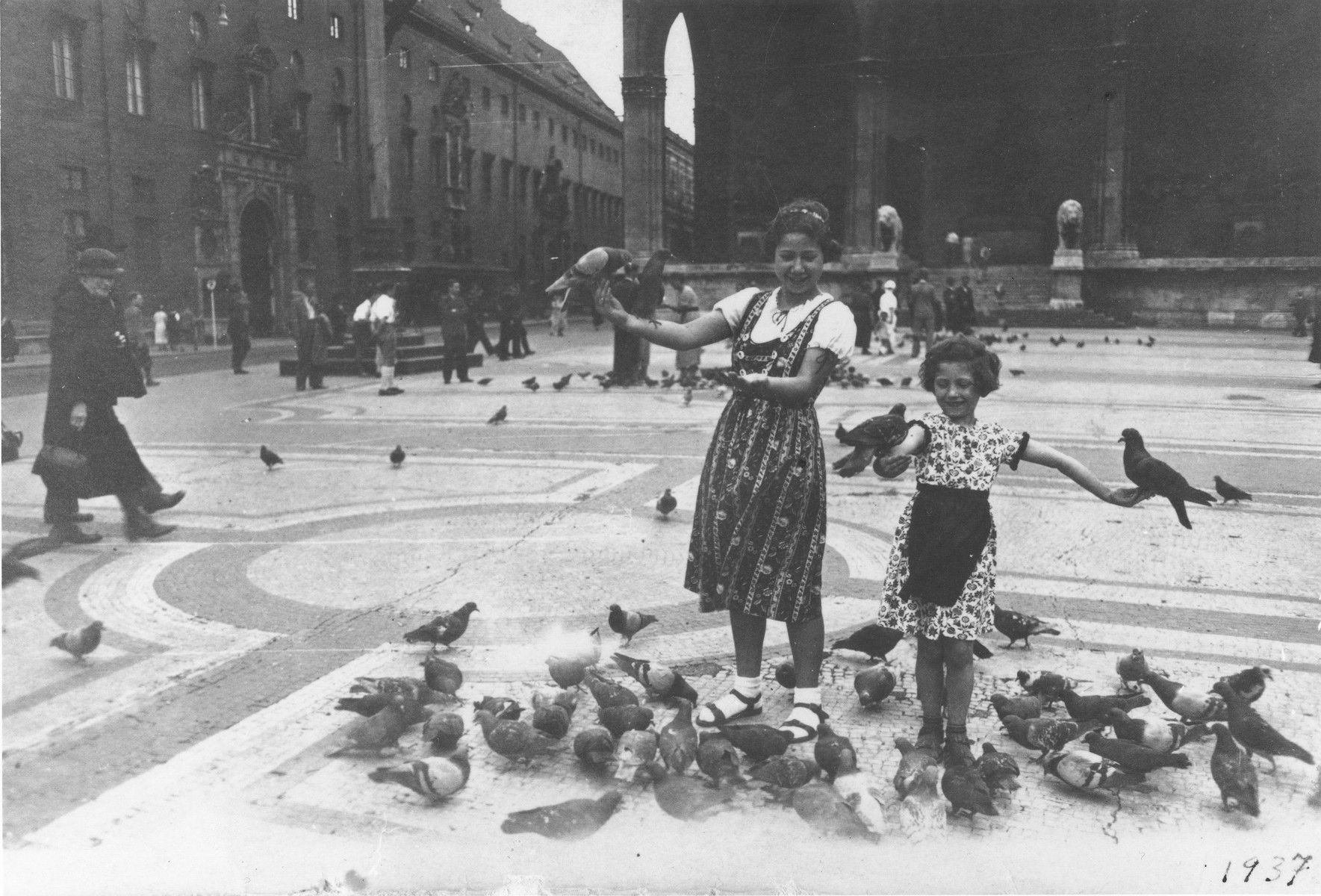 Berta and Inge Engelhard play with the pigeons in front of the Feldherrenhalle in Munich.