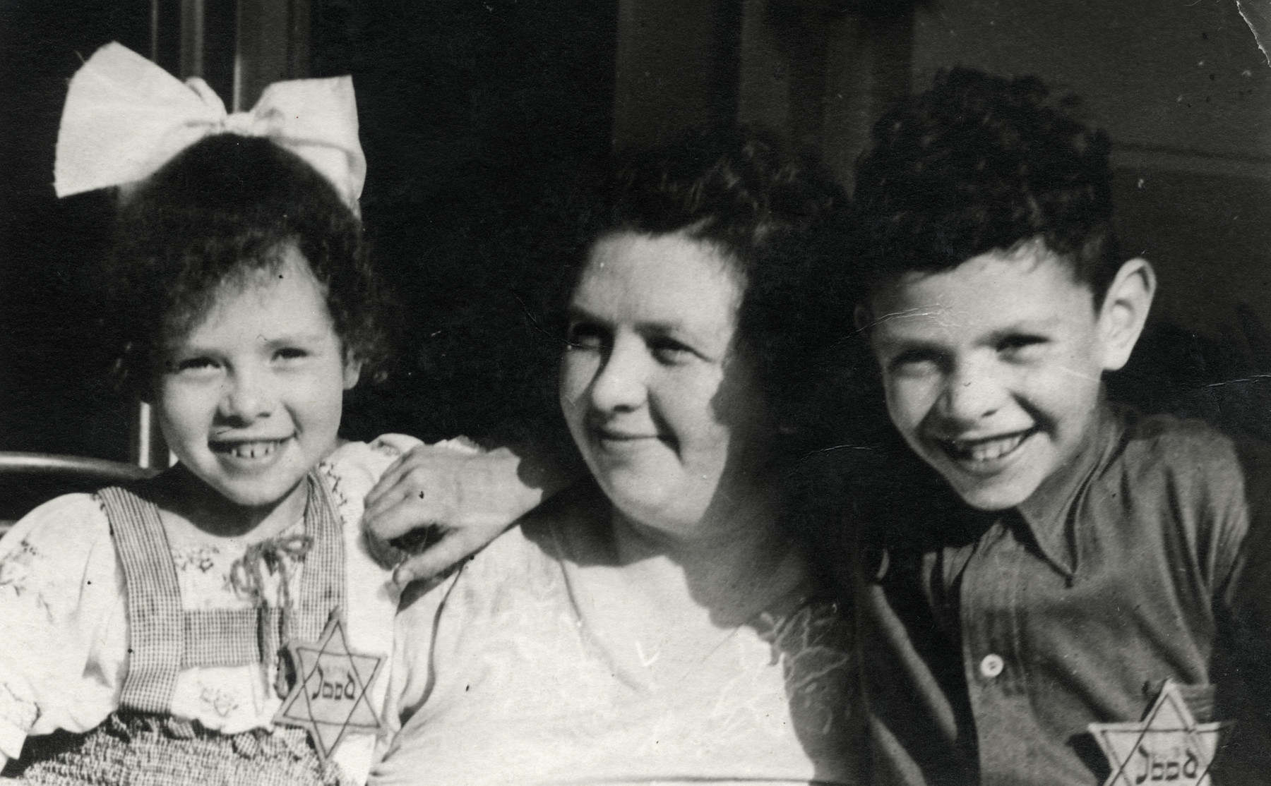 Close up portrait of the Elly, Erna and Alfred Drukker wearing stars of David.