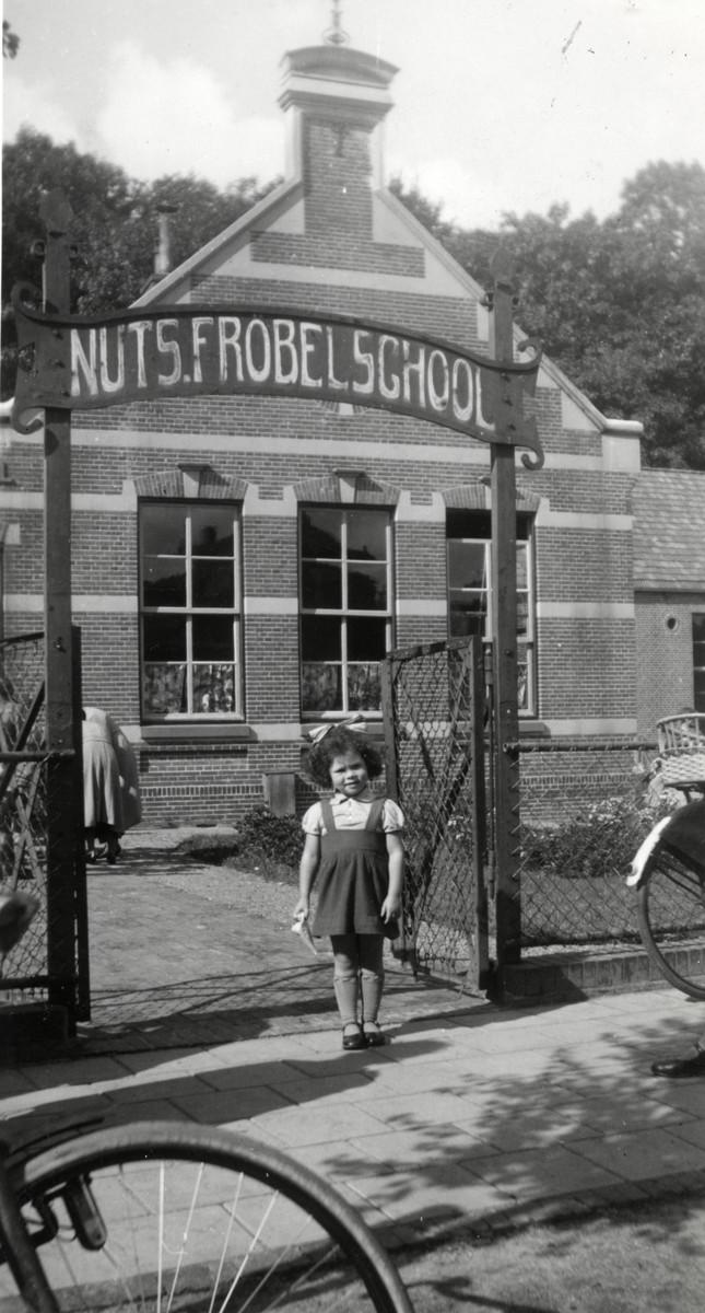 Elly Drukker poses next to the entrance of the kindergarten in Winschoten.