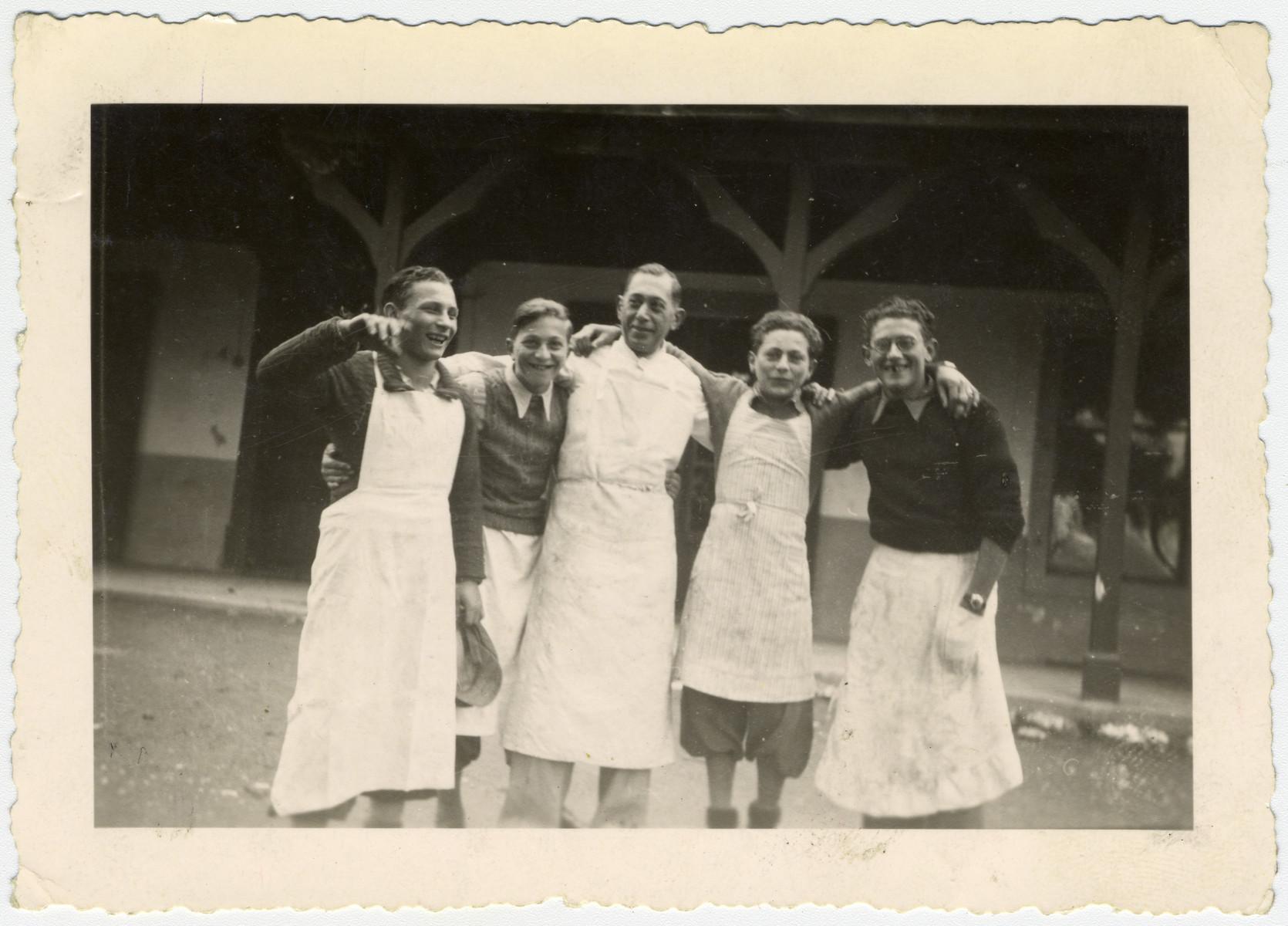 """Group portrait of """"Buchenwald Boys"""", teenage survivors of Buchenwald, wearing chefs' aprons in a children's home in Switzerland."""