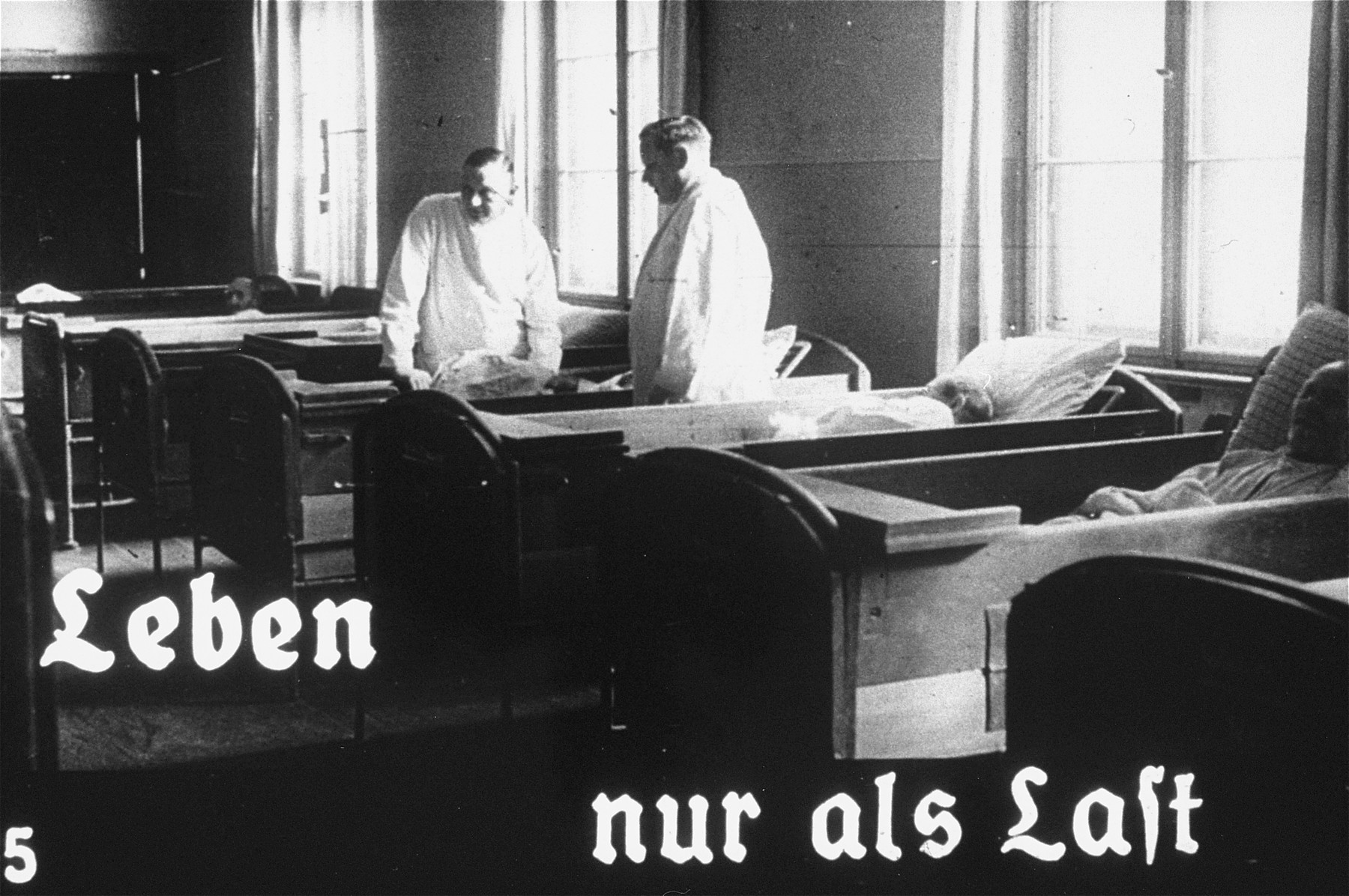 "Propaganda slide featuring two doctors working at an unidentified asylum for the mentally ill.  The caption reads, ""Life only as a burden."""