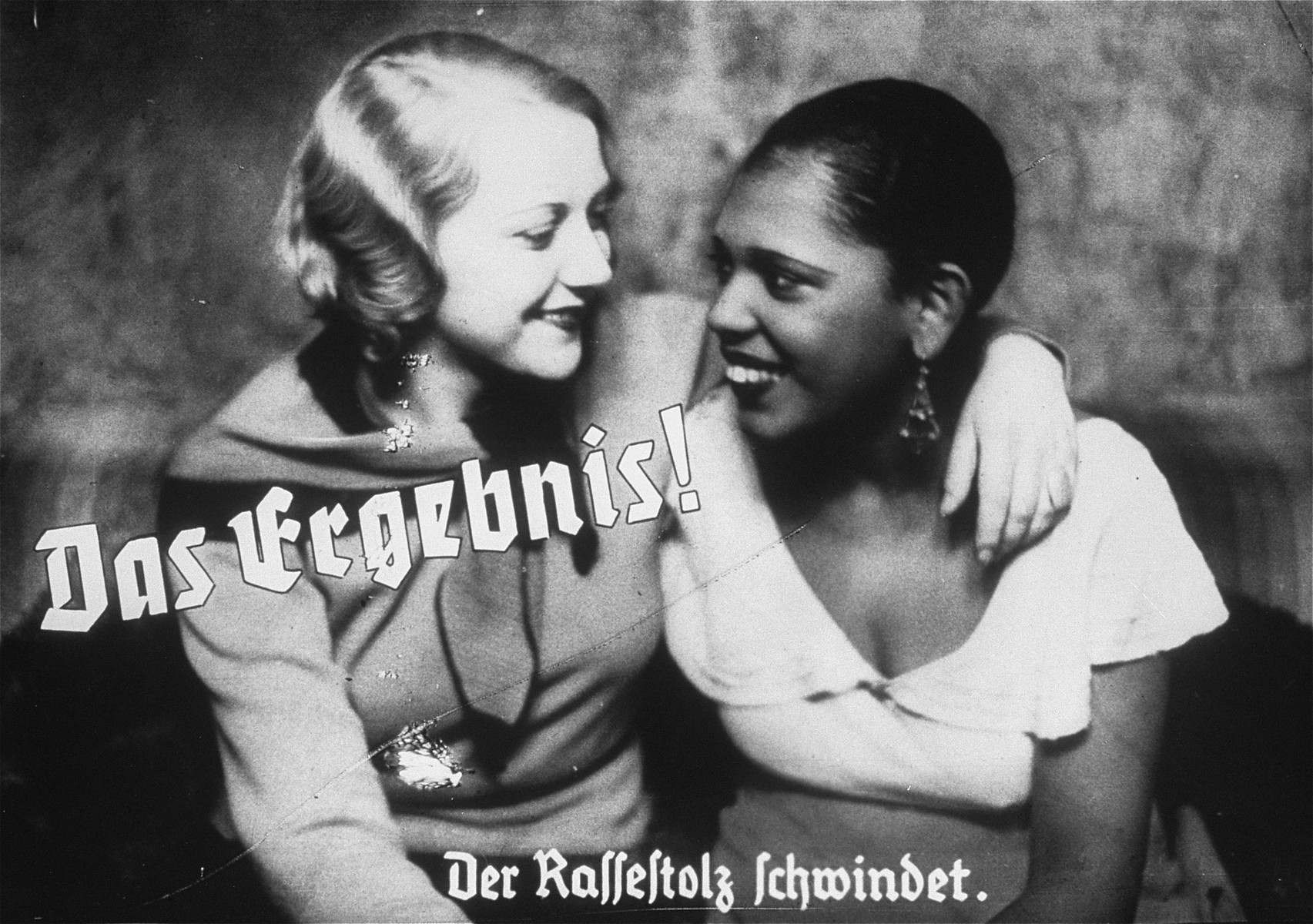 "Propaganda slide depicting friendship between an Aryan woman and a black woman as a loss of racial pride.  The caption reads, ""The result/Racial pride fades."""