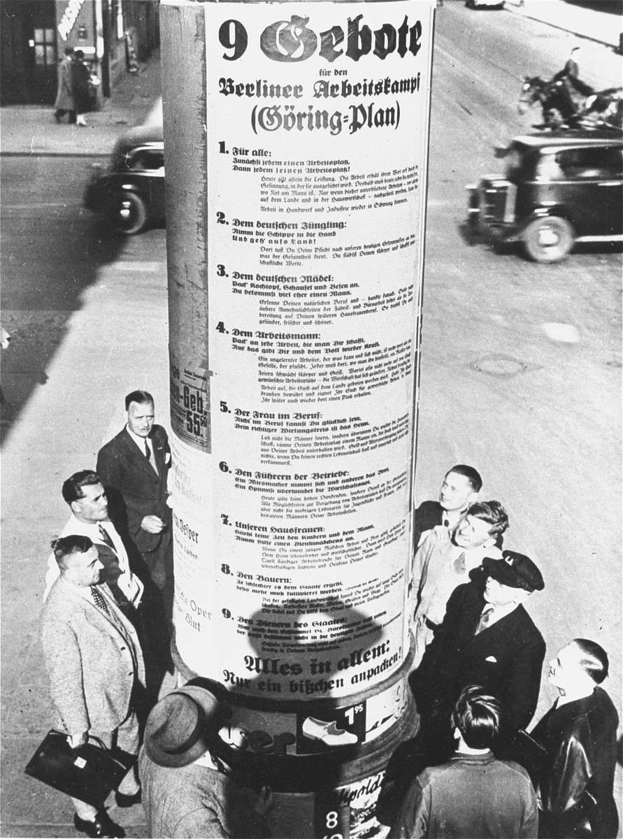 "German pedestrians read a giant poster of Goering's ""Nine Commandments for the Workers' Struggle,"" that has been affixed to a pillar in central Berlin.  The text of the Goering plan reads:  1.  For everyone:  A job for everyone and everyone in his job. 2.  To the German youth:  Take a shovel in hand and go out into the land! 3.  To the German woman:  Take hold of the cooking pan, dust pan and broom and marry a man. 4.  To the working man:  Take on any job that comes your way; only this will give you and the people back its strength. 5.  To women with professions:  You cannot be happy in a profession when your proper place is in the home. 6.  To the union leaders:  A pessimist takes his own bread and that of the others; an optimist overcomes the depression. 7.  To our women at home:  Do not take time from your children and your husband, accept the help of a maid. 8.  To the farmers:  The more difficult the state makes it, the more that must be cultivated. 9.  To the civil servant:  [unreadable] Everyone in everything: Just take on a bit [of work]."
