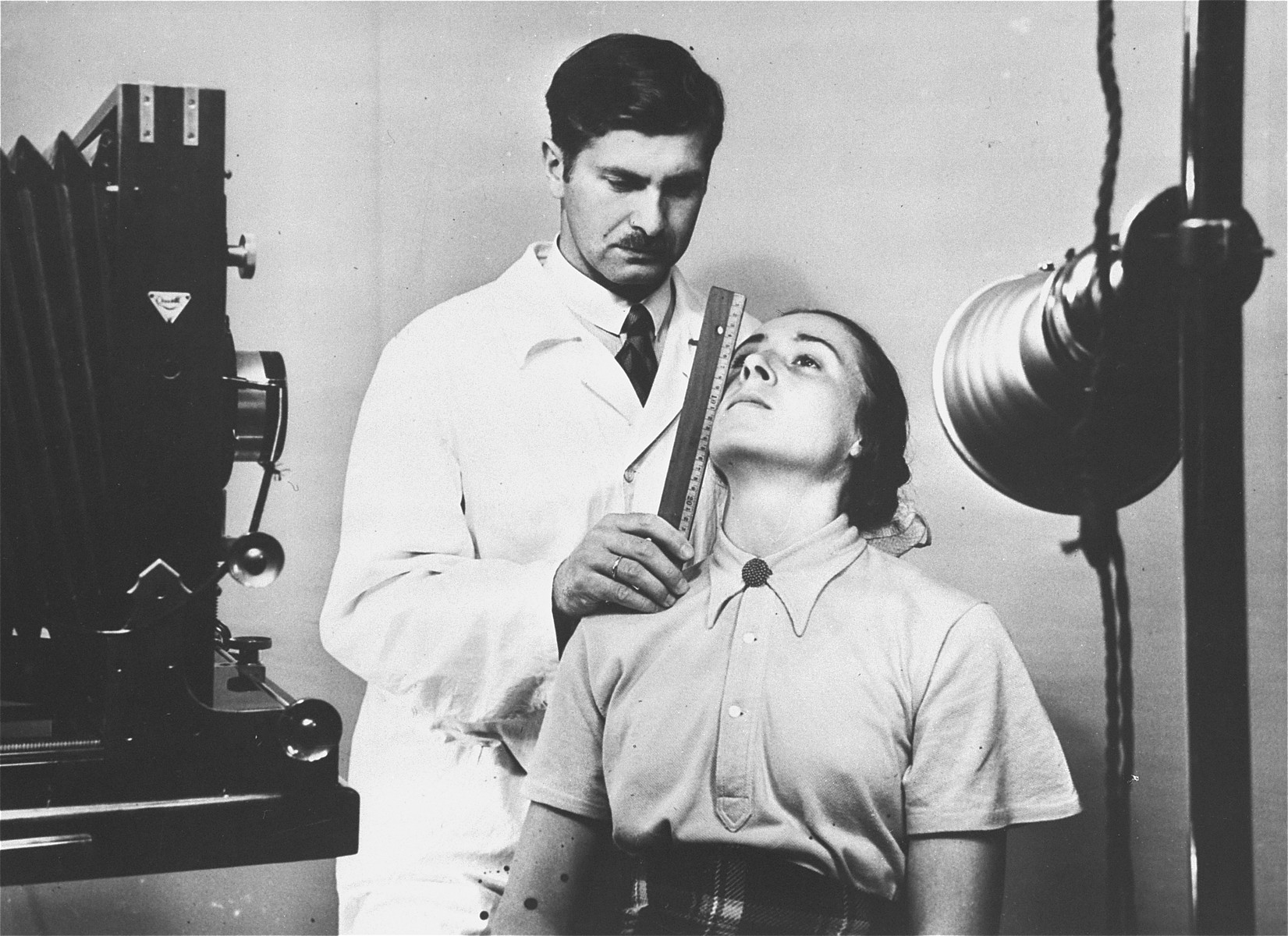 The facial features of a young German woman are measured during a racial examination.