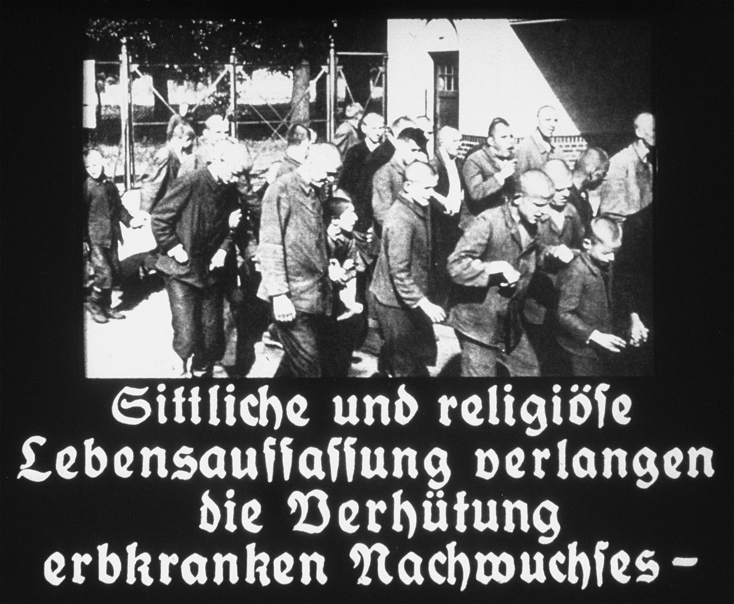 """Propaganda slide featuring a a group of mentally ill patients being escorted outside in an unidentified asylum.  The caption reads, """"Moral and religious concepts of life demand the protection of the congenitally ill."""""""