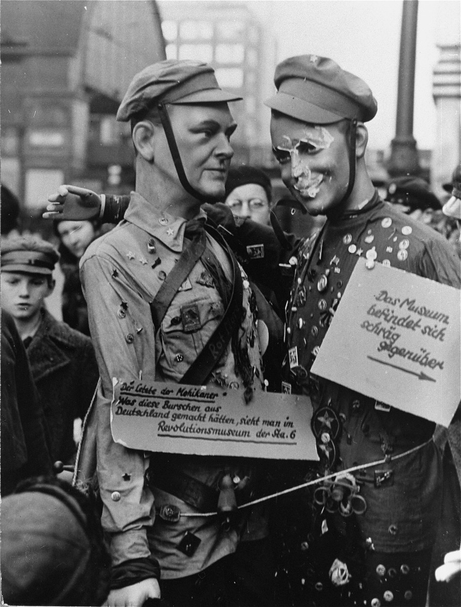 """Two mannequins in the uniform of the Communist """"Red Front"""" displayed in the Alexanderplatz as a promotion for the National Socialist Museum  of Revolution.   The photo shows the two dolls with placards reading: """"`The Last of the Mohicans': What these lads would have made out of Germany, is to be seen at the Museum of Revolution, of the Standard 6""""."""