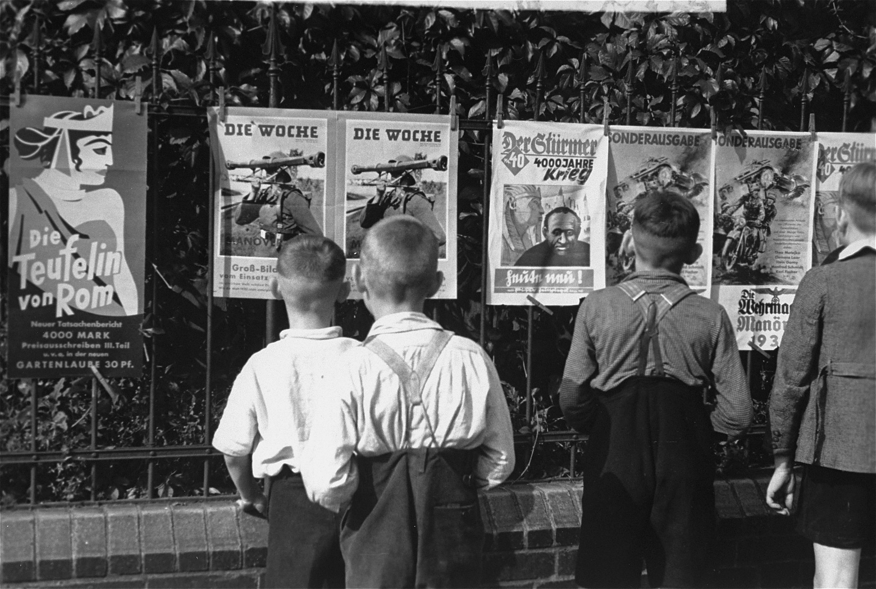 """A group of young German boys view """"Der Stuermer,"""" """"Die Woche,"""" and other propaganda posters that are posted on a fence in Berlin."""