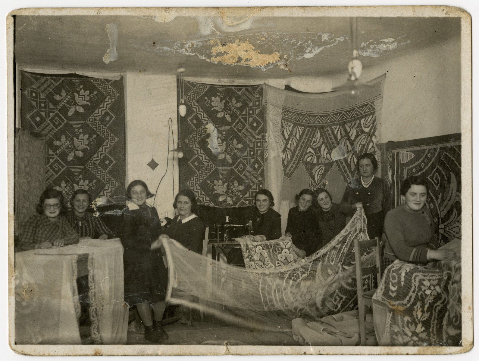 A group of Beit Yaakov women sew lace curtains in Rymanow, Poland.  Pictured at the right is the donor's mother, Sara Ginsburg Keller.
