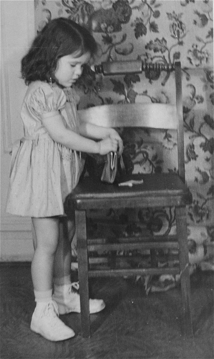 Portrait of the donor, Haviva Kaplan, as a young girl playing with a purse in her home in New York.