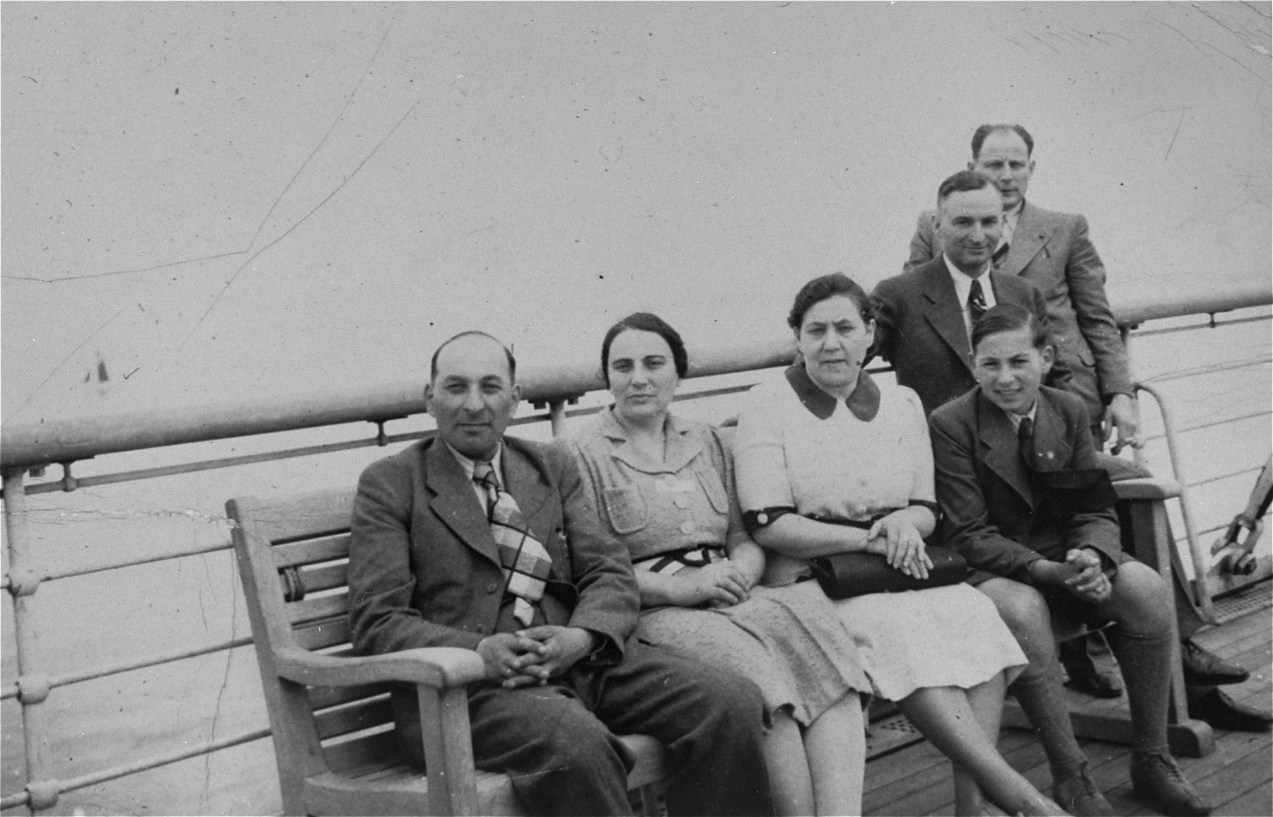 A Jewish refugee family from Germany poses on the deck of the SS Rotterdam while en route to New York.  Pictured are Sol and Henrietta Meyer (seated on the left) and their son Harvey (seated at the right).  (The Meyers are the aunt and uncle of donor Jill Pauly.)