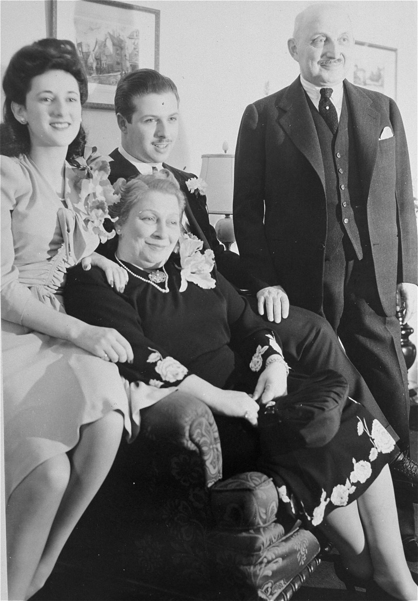 A family of Jewish refugees from Belgium poses in their home in New York during World War II on the occasion of the wedding of Helene Ginsburg to William Friedman.  From left to right:  Helene Ginsburg, Deborah Friedmann, William Friedman and Joseph Friedmann.