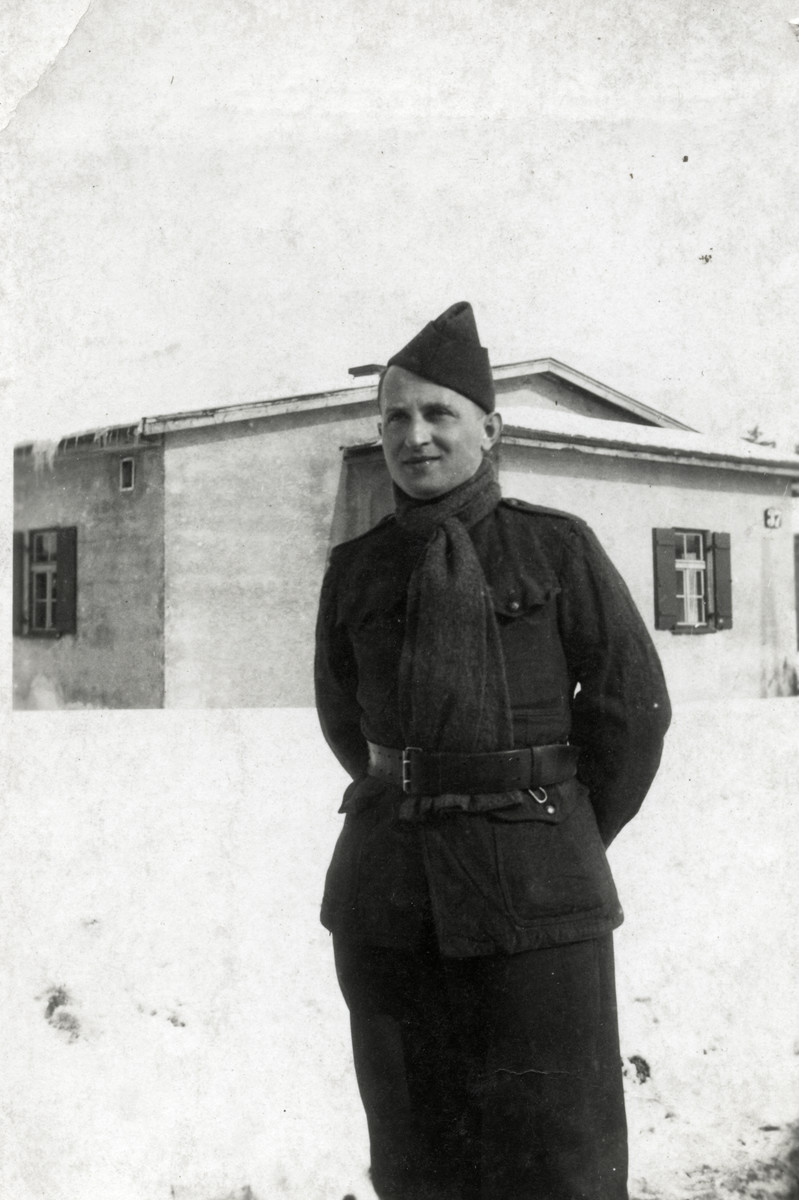 Mendel Einhorn stands outside a barrack in the snow in a prisoner of war camp in Germany.