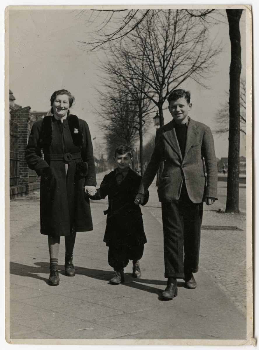 Sura Rubinstein walks down a street in the Berlin-Schlachtensee displaced persons camp together with her two sons.  From left to right are Sura, Benny and Nathan Rubinstein.