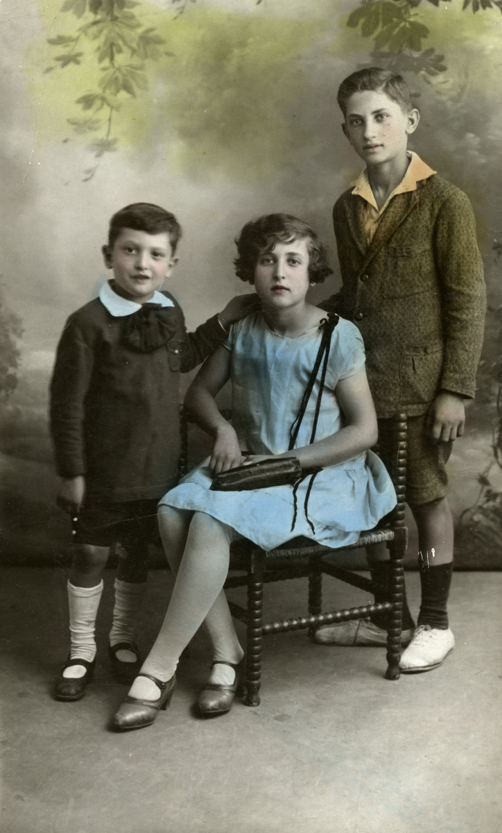 Colorized studio portrait of three Jewish siblings in Paris.  From left to right are Maurice, Miriam and Charles Einhorn.
