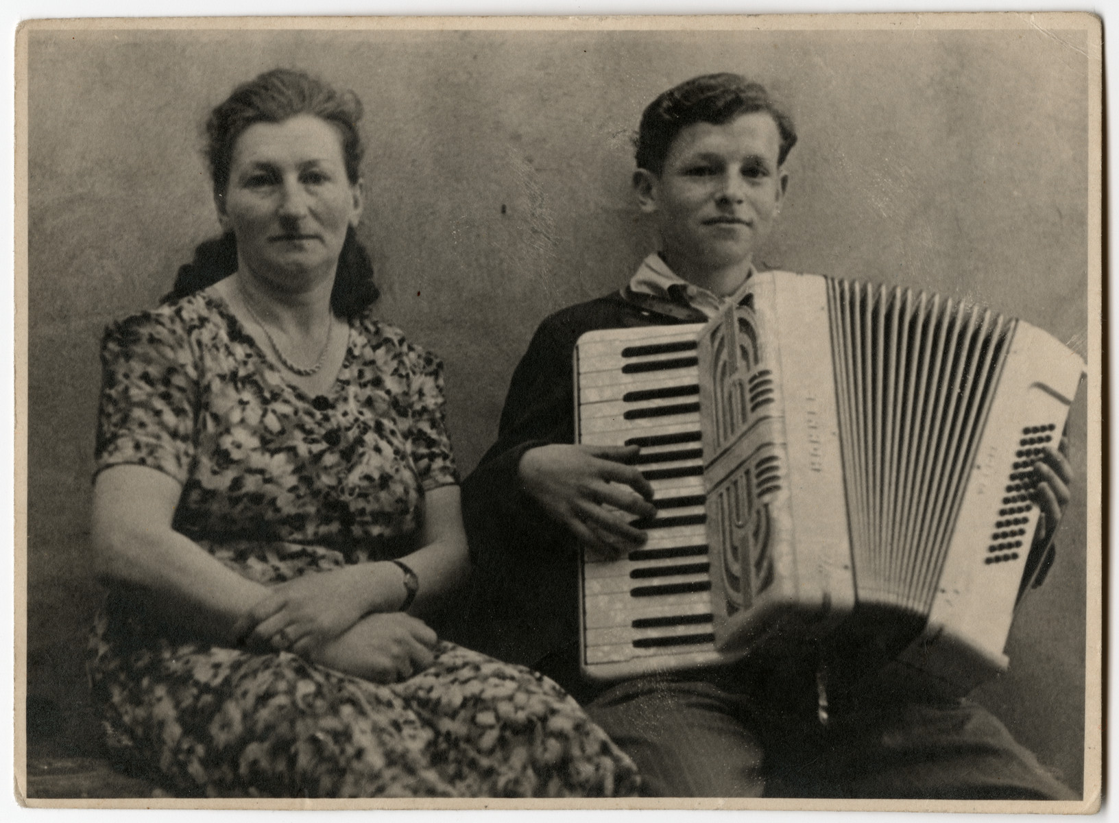 Nathan Rubinstein plays the accordion while his mother sits and listens.