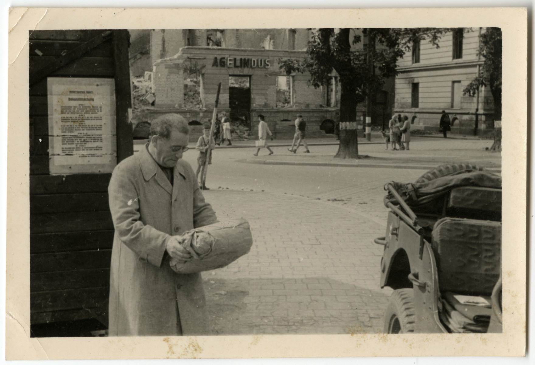 Dr. Hirsch (Tzvi) Elkes stands on a street corner in Germany and examines a package.