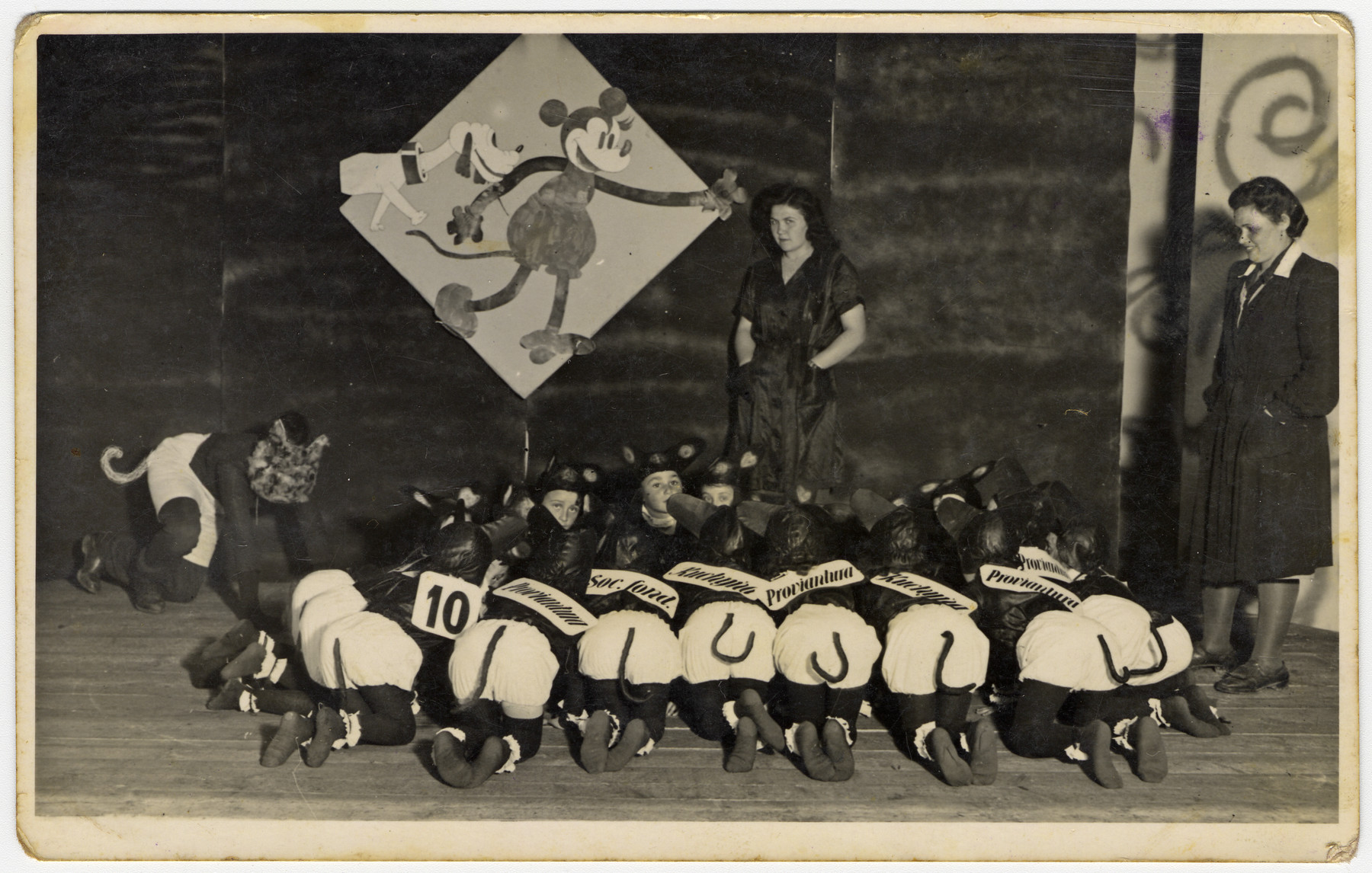 Children dressed as mice perform a play about Mickey Mouse in the Novaky labor camp.  Among those pictured is Mira Menzer (second row, far right).