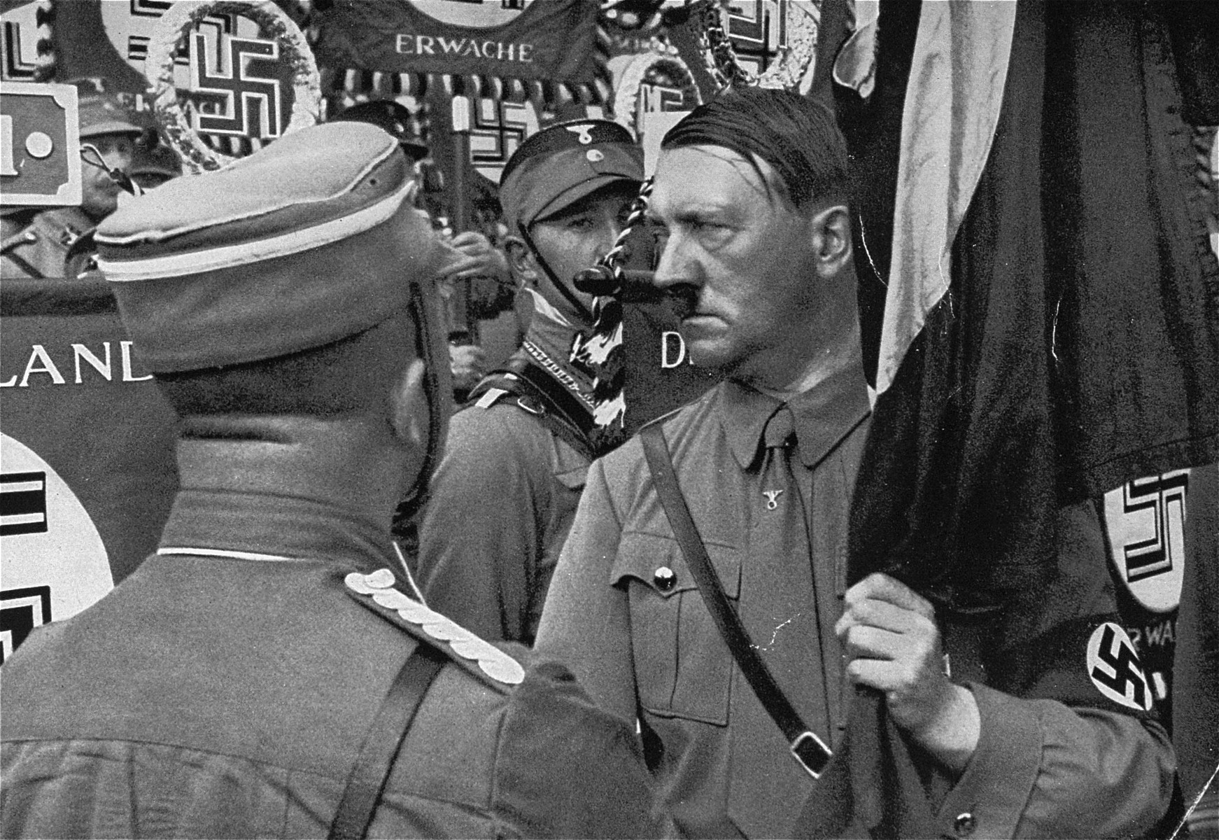 "Grasping the ""Blood Flag"" in his hand, Adolf Hitler moves through the ranks of SA standard bearers at a 1934 Reichsparteitag (Reich Party Day) ceremony."