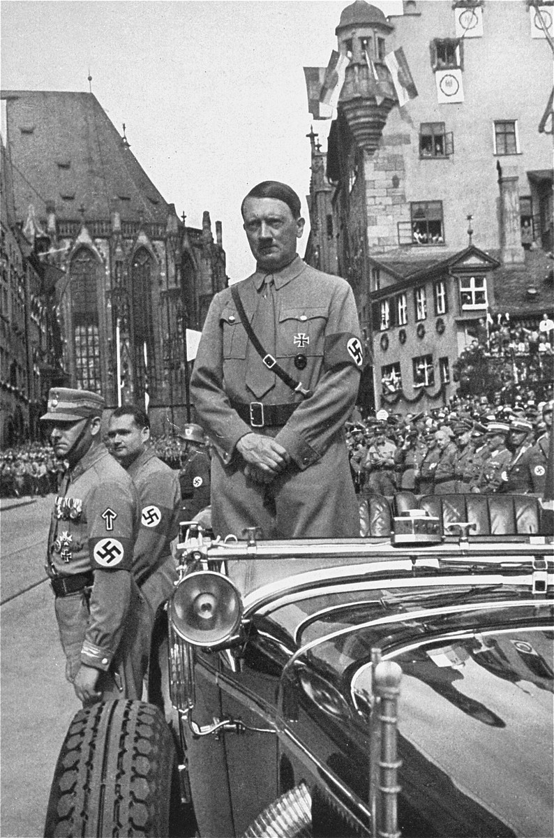 Standing in his car, Adolf Hitler waits to review the next column of passing SA troops during a Reichsparteitag (Reich Party Day) parade.