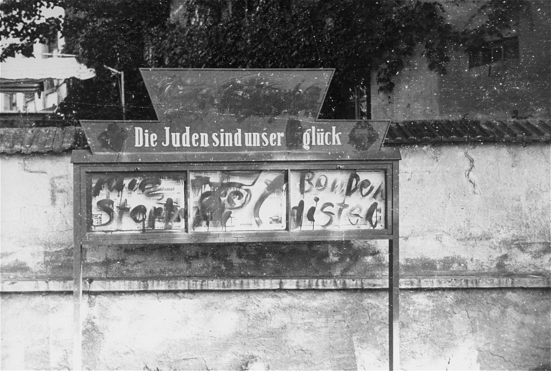 "A display box for the ""Der Stuermer"" newspaper that has been defaced to read, ""The Jews are our fortune"" instead of ""The Jews are our misfortune""."