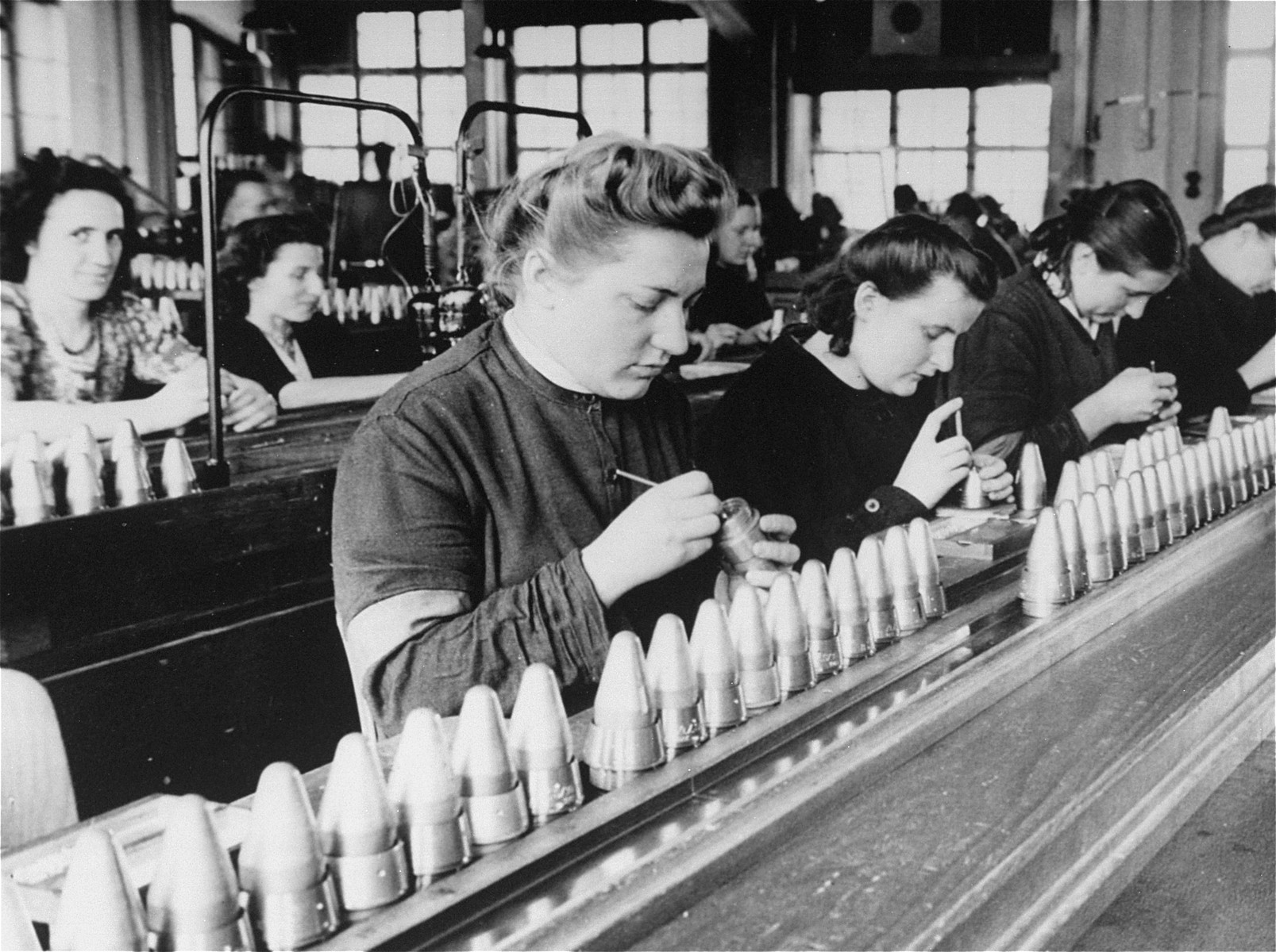 Female foreign workers (in dark clothing) from the Stadelheim prison work in a factory owned by the AGFA camera company.  This photograph was submitted in evidence as part of the case against I.G. Farben.