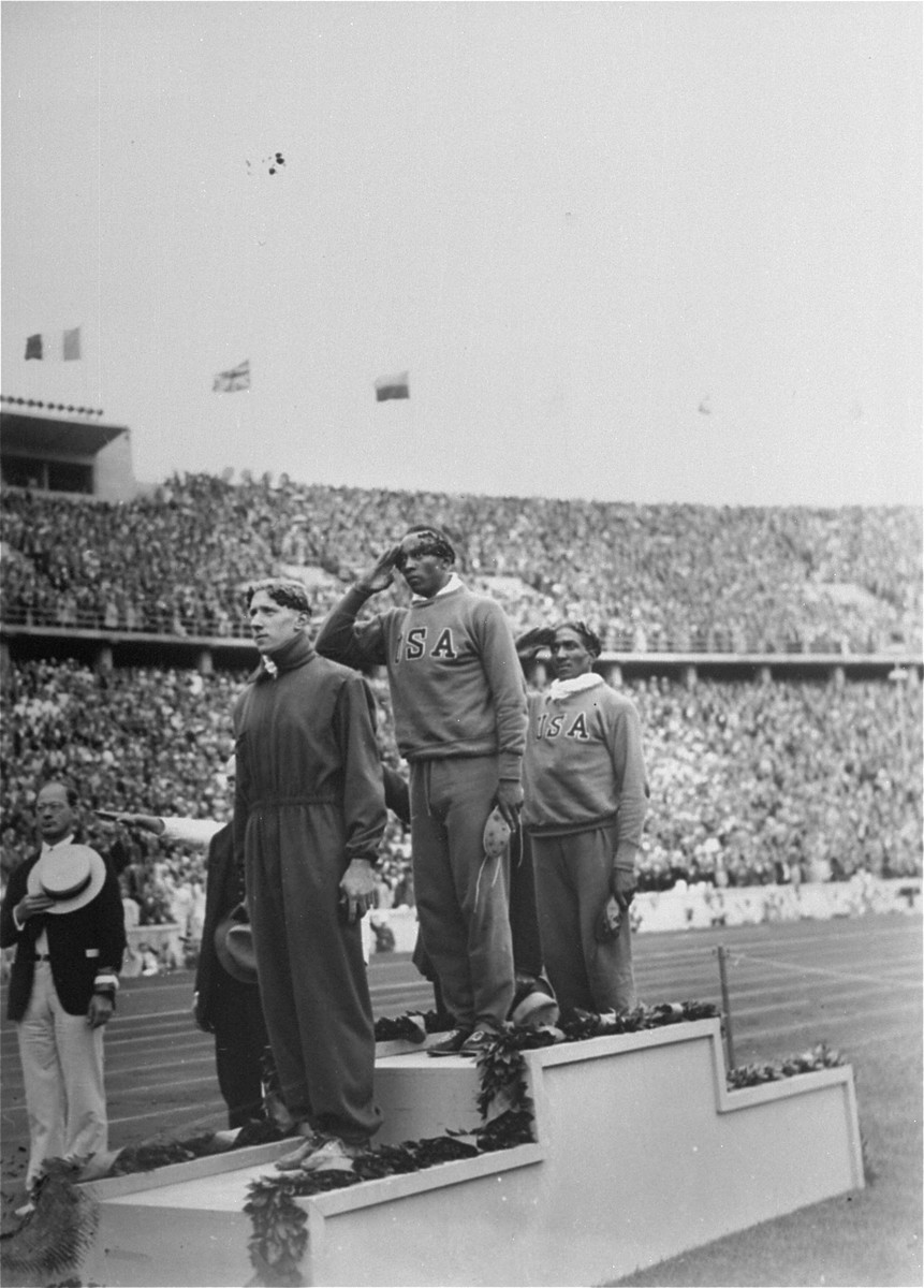 The winners of the 100m dash on the medal stand at the 11th Summer Olympic Games.   Saluting, are Jesse Owens (Gold), and Ralph Metcalfe (Silver). The Bronze went to M. B. Osendarp of Holland. Owens set a new record in the event recording a 10.2 time which was disallowed by German officials who claimed Owens had benefitted from a tailwind.