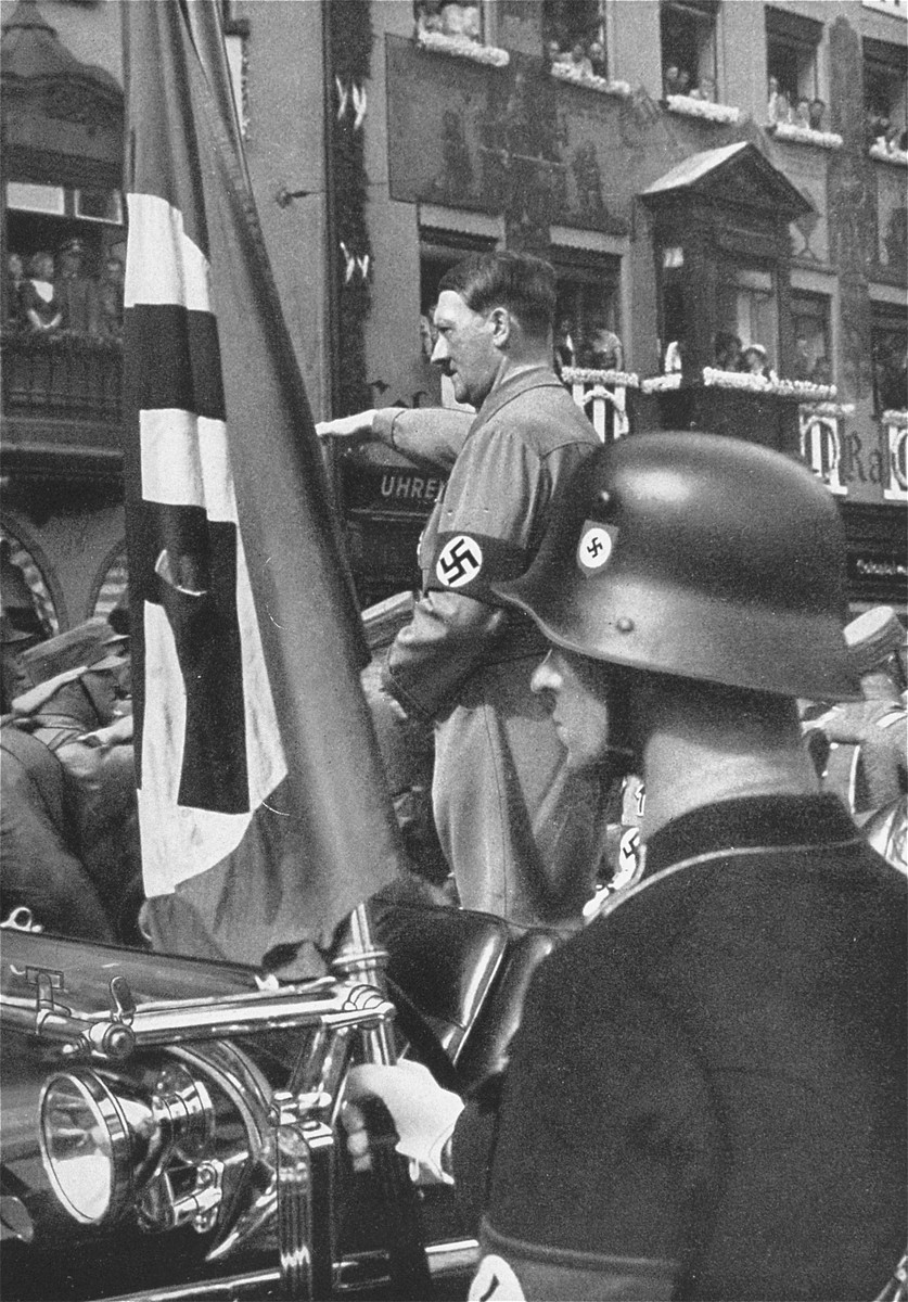 "Adolf Hitler salutes passing SA formations at the sixth Reichsparteitag (Reich Party Day) in Nuremberg.  The ""blood flag"" from the 1923 putsch is pictured in the foreground."