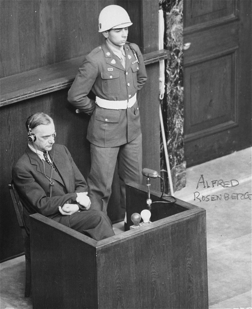 Former Nazi Party ideologist Alfred Rosenberg in the witness box at the International Military Tribunal war crimes trial at Nuremberg.  Emilio DiPalma  is the military policeman standing guard next to him.