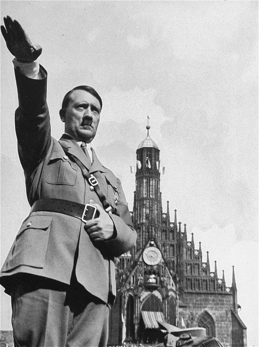 Adolf Hitler salutes the crowd from his open car during the Reichsparteitag (Reich Party Day) parade in Nuremberg.