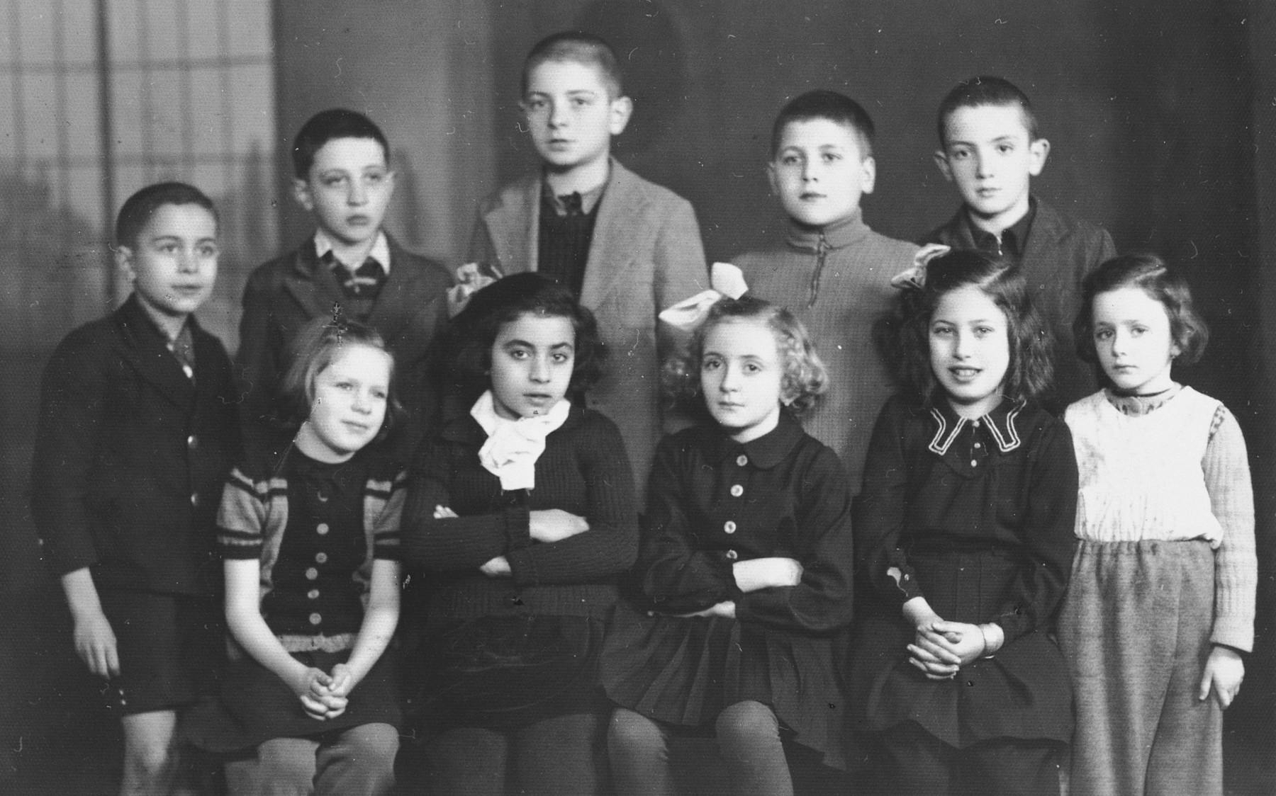 Group portrait of third-grade children in the Jewish school in Plovdiv, shortly before liberation.  Seated from left to right are Bott, Ruti Garti, Becky, Daisy, unknown, and Amy Garti.  Standing from left to right are Alexander (Sender), Emanuel Tchitchekik, Avram Ben Arroya, Nissim Majar, and Yitzhak Kobo.