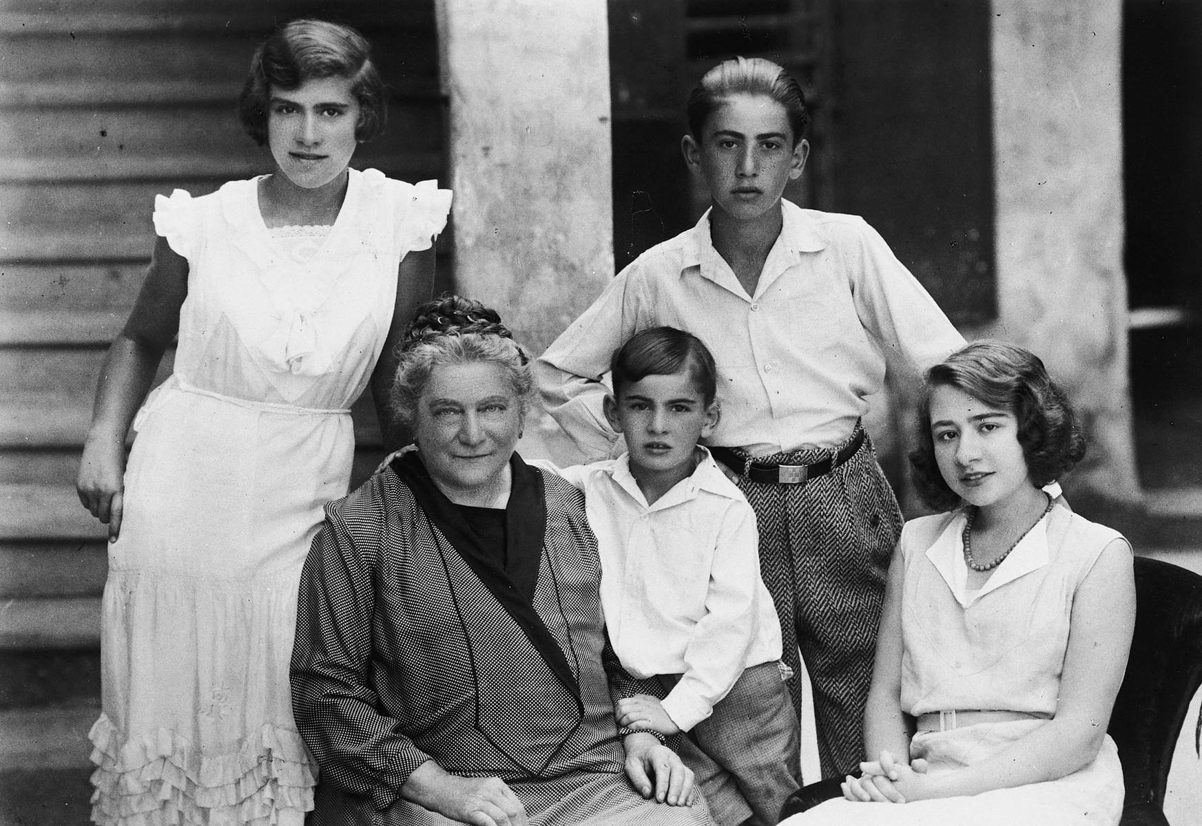 An Austrian-Jewish woman sits on the porch of her home surrounded by her grandchildren.  From left to right are Gretl Singer, Therese Porges, Paul Peter Porges, Kurt Porges, and Stella.