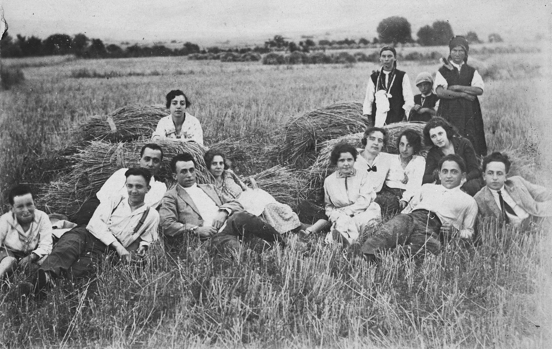 A group of young Bulgarian Jews rests by bundles of hay in the countryside where they have gone to help with the harvest.  In the back are three Bulgarian villagers.  Seated on the right are David, Gisela and Julia Tchitchekik.