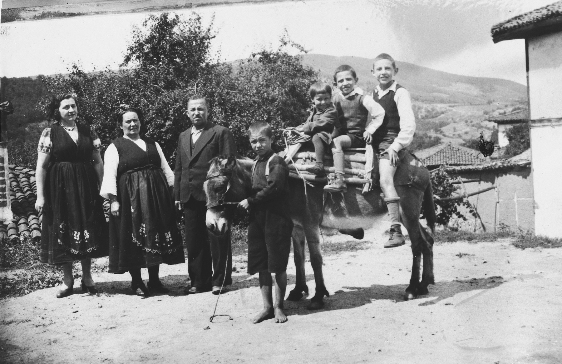 The Tchitchekik family poses with local villagers in the village where they are spending their summer vacation.  Gisela Tchitchekik is on the far left.  Her sons, Emanuel and Yitzhak, share a donkey ride with another child.