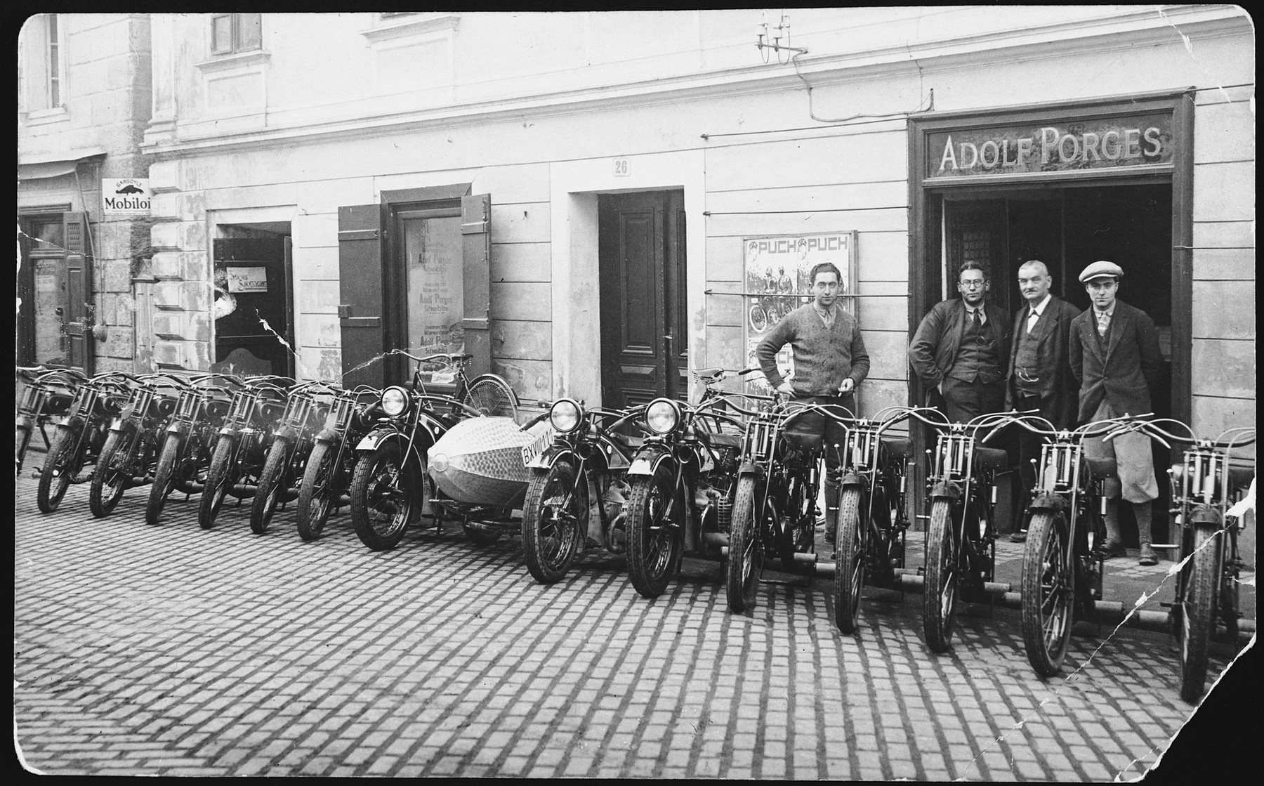An Austrian-Jewish family stands before a row of motorcycles parked in front of their department store.  Pictured are Ernst, Hugo, Joseph and Hermann Porges.
