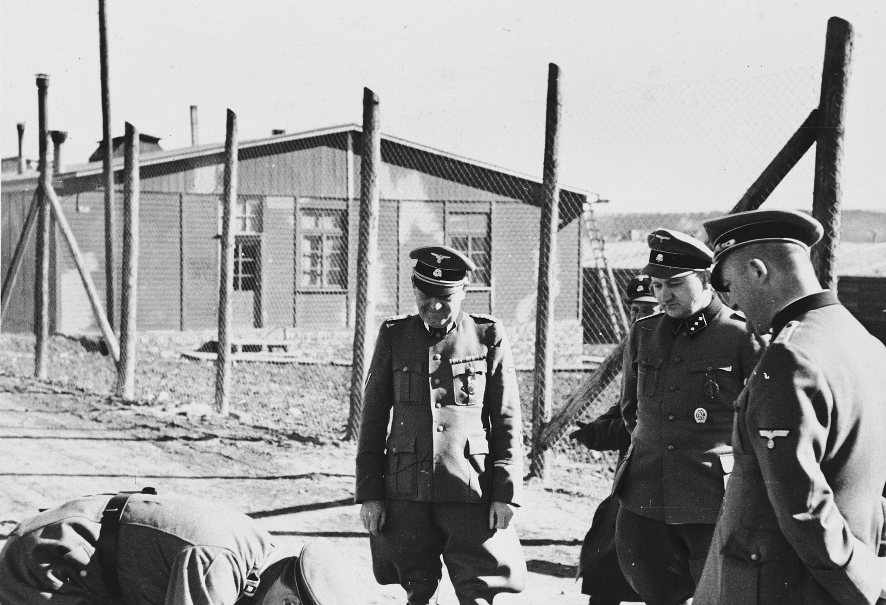 A group of SS officers views something on the ground in the Buchenwald concentration camp.