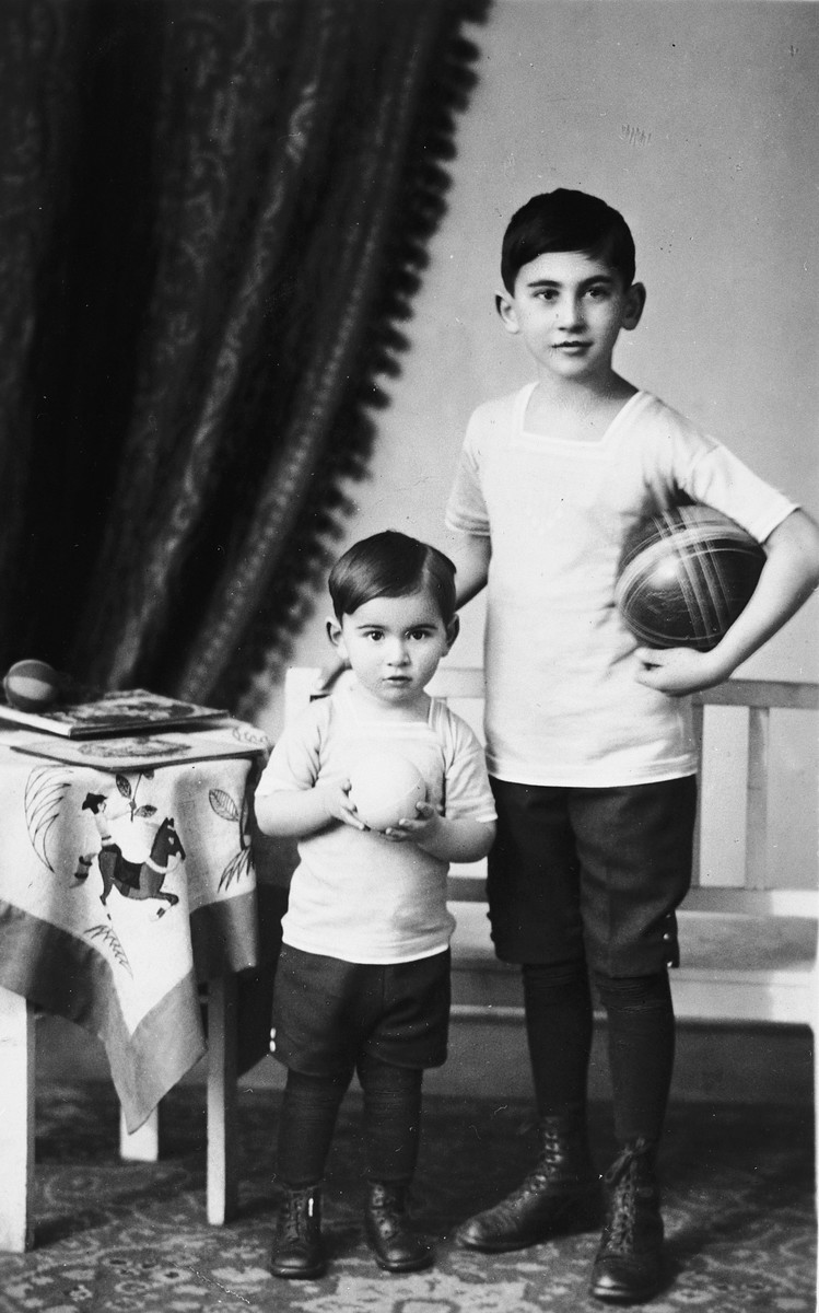 Studio portrait of two Austrian-Jewish brothers, Kurt and Paul Peter Porges, holding balls.