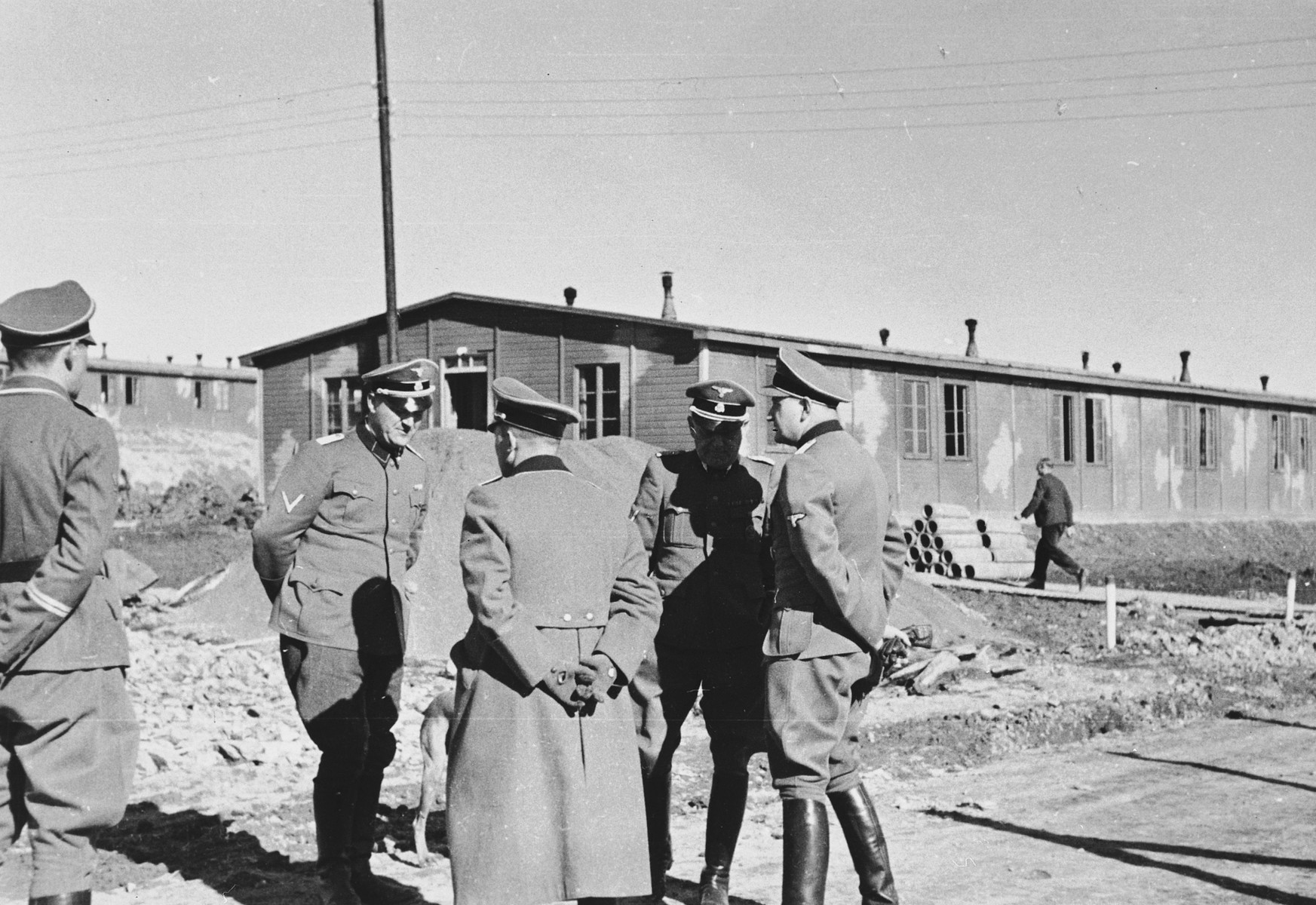 A group of SS officers converse outside at a construction site in the Hinzert concentration camp.