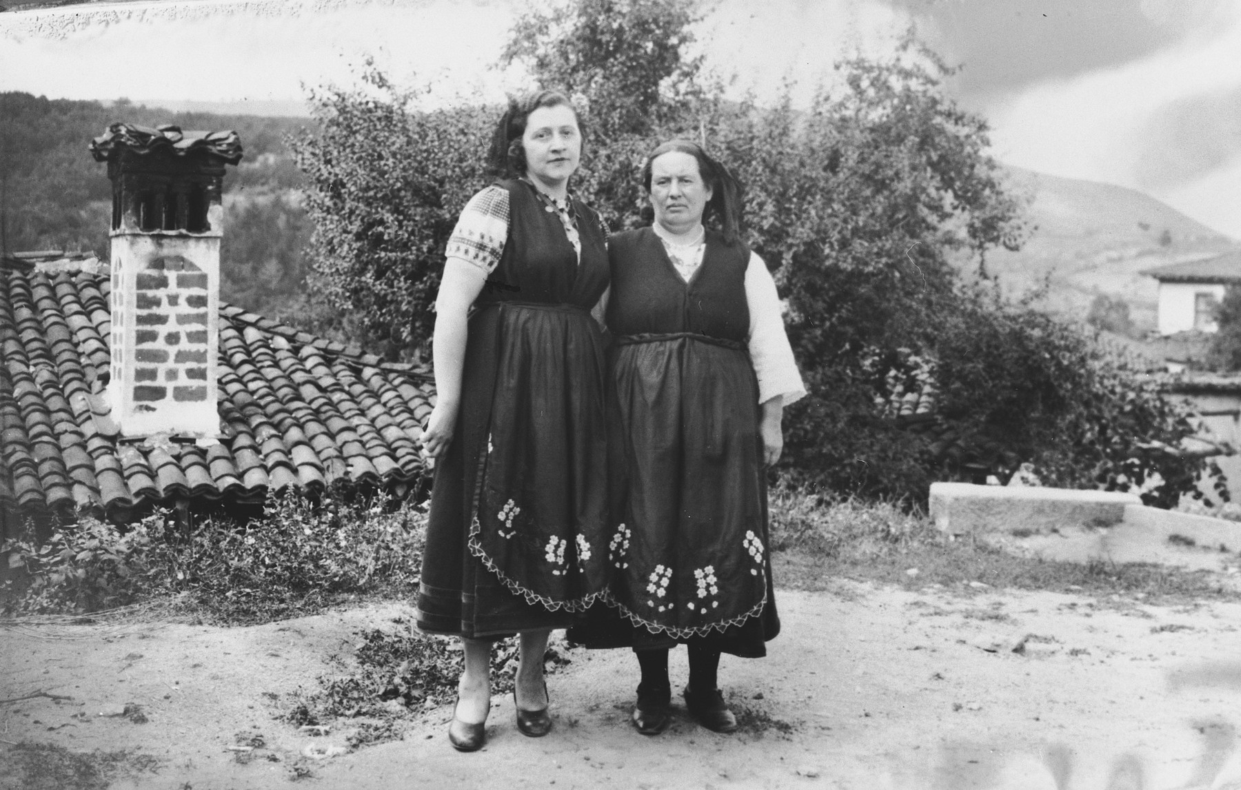 Gisela Tchitchekik (left) and a village woman pose together in matching traditional costumes in the village where Gisela and her sons are spending their summer vacation.