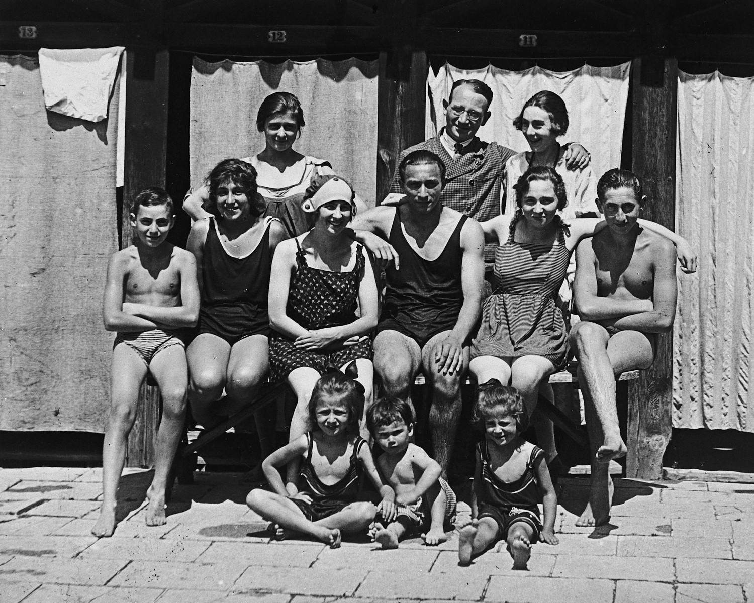 An extended Austrian-Jewish family poses for a family portrait in their bathing suits.  Pictured are the Porges family.  Paul Peter is the youngest child in the front center.  His mother, Jenny Porges, is pictured in the second row, third from the left.