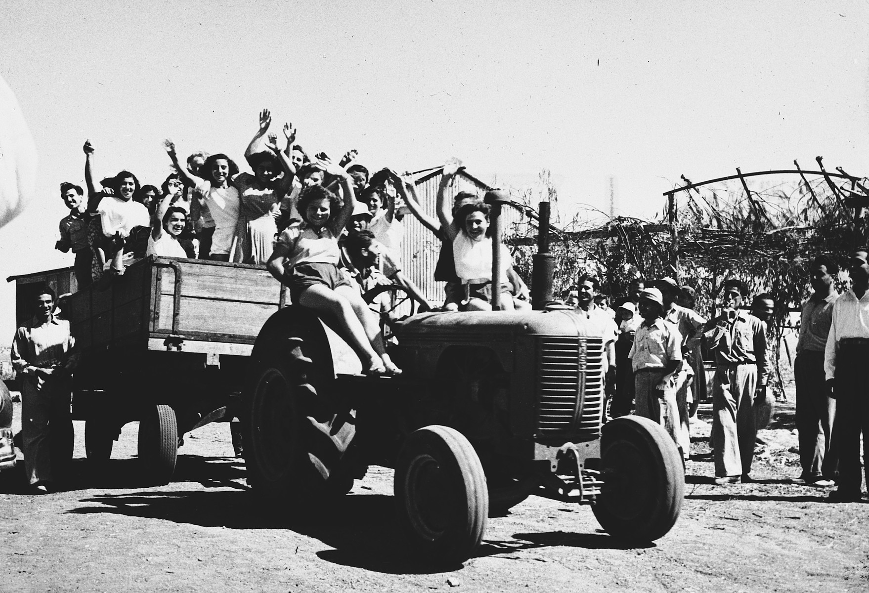 Teenage girls wave from a wagon pulled by a tractor in Tel Shachar.