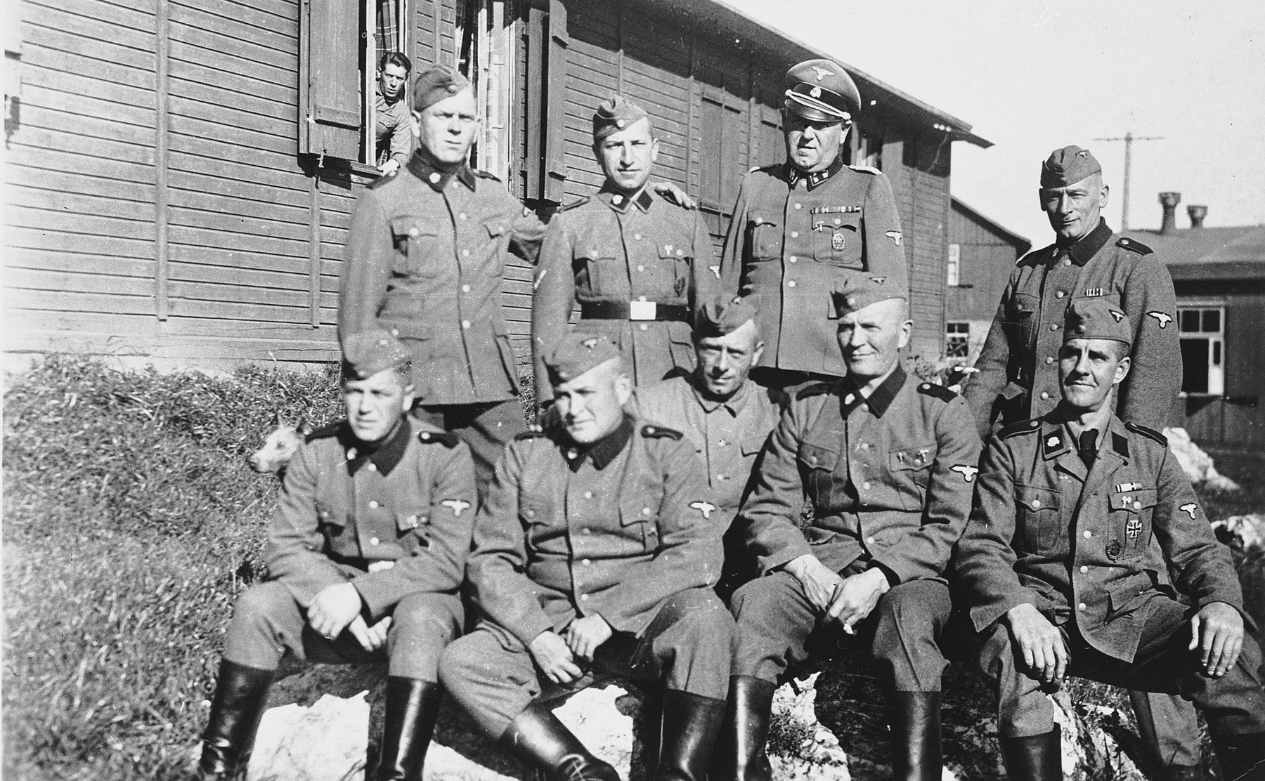 Group portrait of SS men with an officer in front of a barrack in the Hinzert concentration camp.  Standing in the center is Hermann Pister.