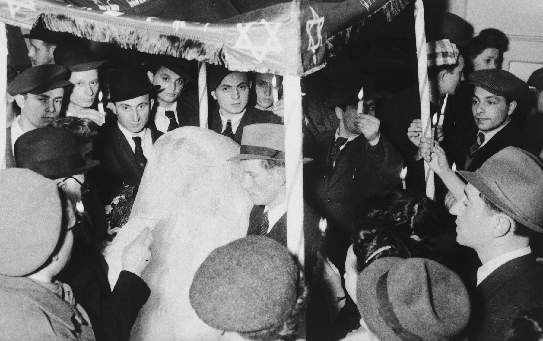 Bela Milstein and Jacob Gutman stand under a chuppa [wedding canopy] during their marriage ceremony in the Mittenwald displaced persons' camp.  This was the first Jewish wedding to be held there.