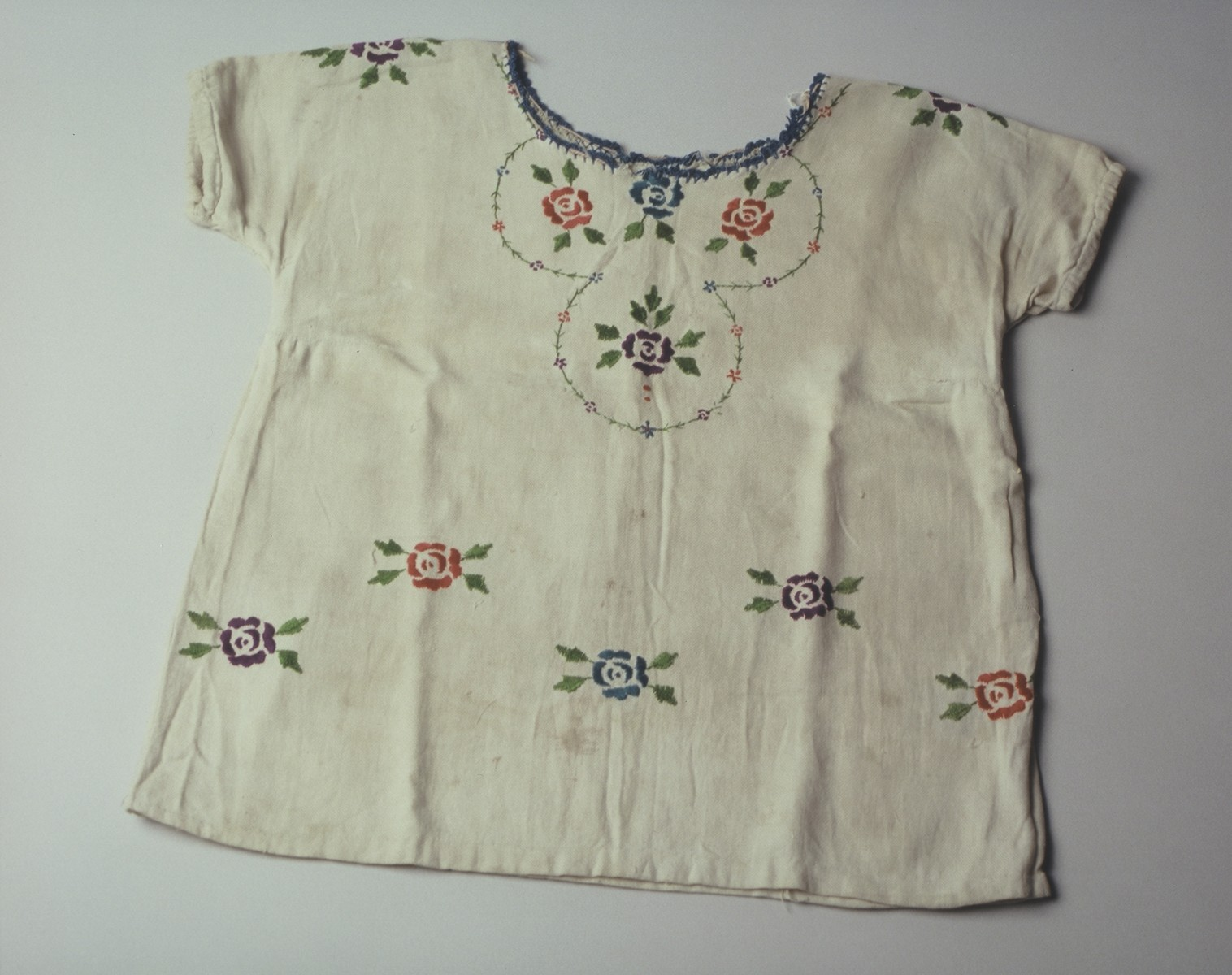 A child's dress embroidered with red and blue flowers with small green leaves.    The dress was hand embroidered by Lola Kaufman's mother in the Czortkow ghetto and worn by Lola in hiding.