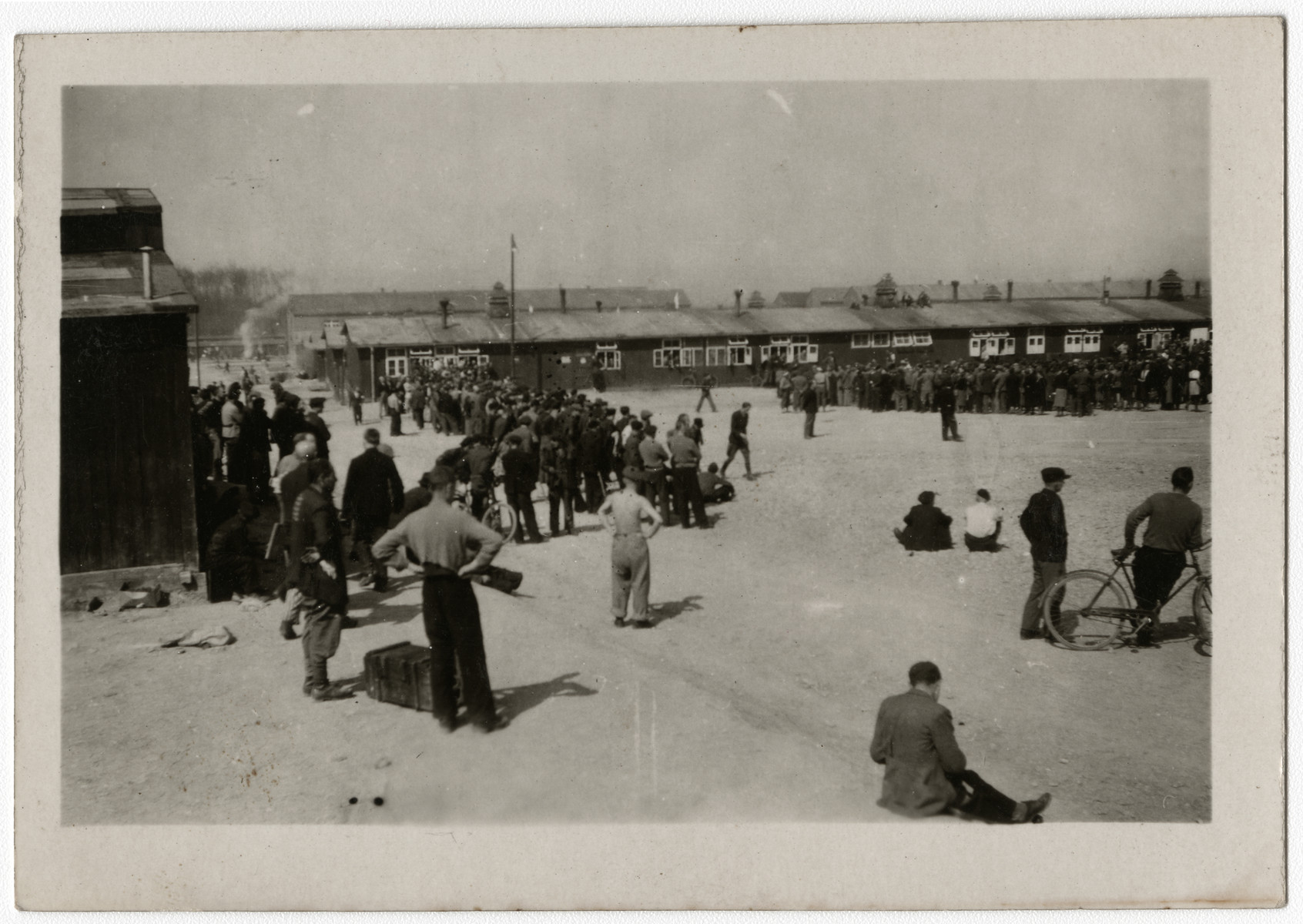 """German civilians are marched through the Buchenwald concentration camp while survivors look on.  The original caption reads: German civilians (inner circle) being shown horrors in Buchenwald concentration camp Germany near Weimar.""""."""