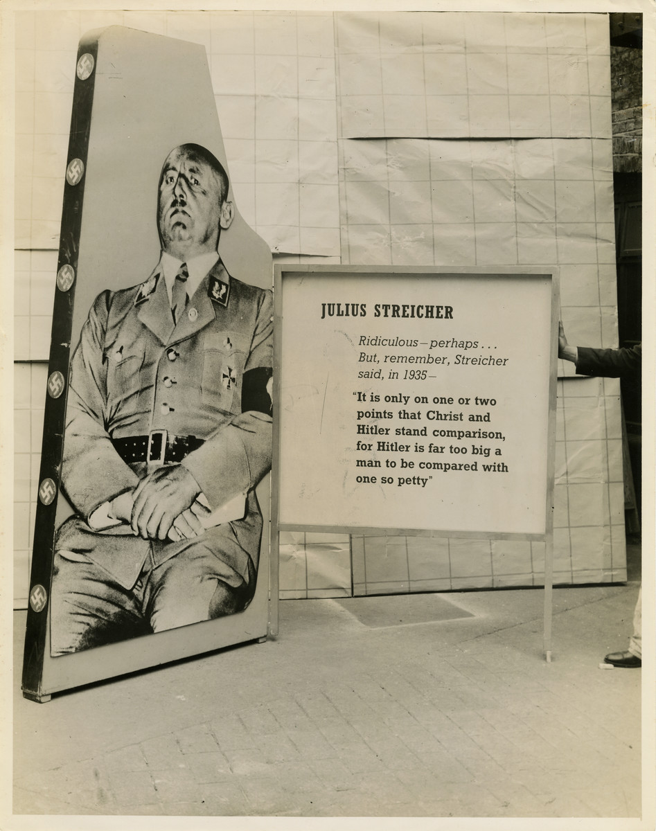 """Panel from a 1944 exhibition in London, England, entitled """"Germany- the Evidence"""" showing Julius Streicher.   The panel reads """"Julius Streicher; Ridiculous- perhaps... But, remember, Streicher said, in 1935- 'It is only on one or two points that Christ and Hitler stand comparison, for Hitler is far too big for a man to be compared with one so petty.'""""   The back of the photo reads """"British Official Photograph; Distrbuted by the Ministry of Information. D. ; The Evil We Fight.; Ministry of Information Exhibition priduced by Display &Exhibitions Division for show all over Great Britain.; Display panel"""""""
