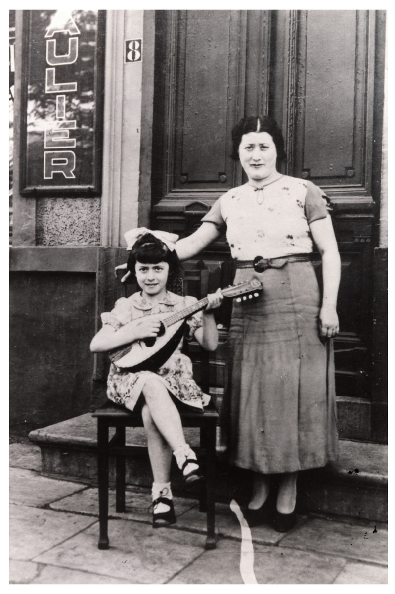 Leah Wajsfelner plays a mandolin while her mother Fajgla stands next to her.