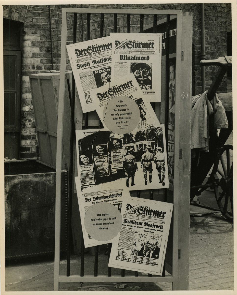 """Panel from a 1944 exhibition in London, England, entitled """"Germany- the Evidence"""" showing antisemitic German Newspapers.   Panel displays numerous antisemitic German newspapers including """"Der Stuermer"""" and """"Der Talmudgerichtshof"""" donning titles such as """"Ritualmord"""" (ritual murder) and """"Praesident Roosevelt"""" (President Roosevelt.""""  The back of the photo reads """"British Official Photograph; Distrbuted by the Ministry of Information. D. ; The Evil We Fight.; Ministry of Information Exhibition priduced by Display & Exhibitions Division for show all over Great Britain.; Display panel"""""""